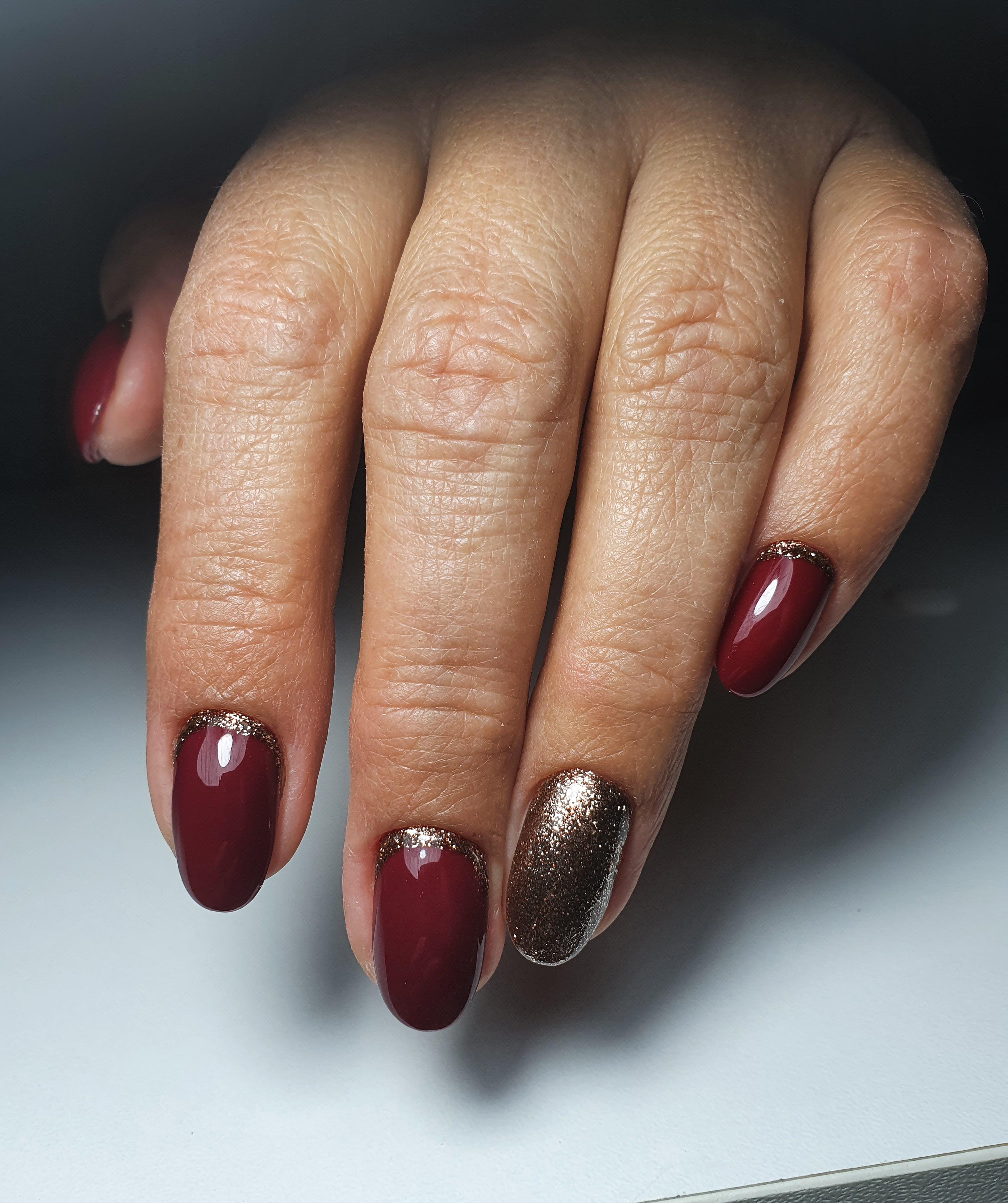 Лунный маникюр с золотыми блестками в темно-красном цвете на короткие ногти.