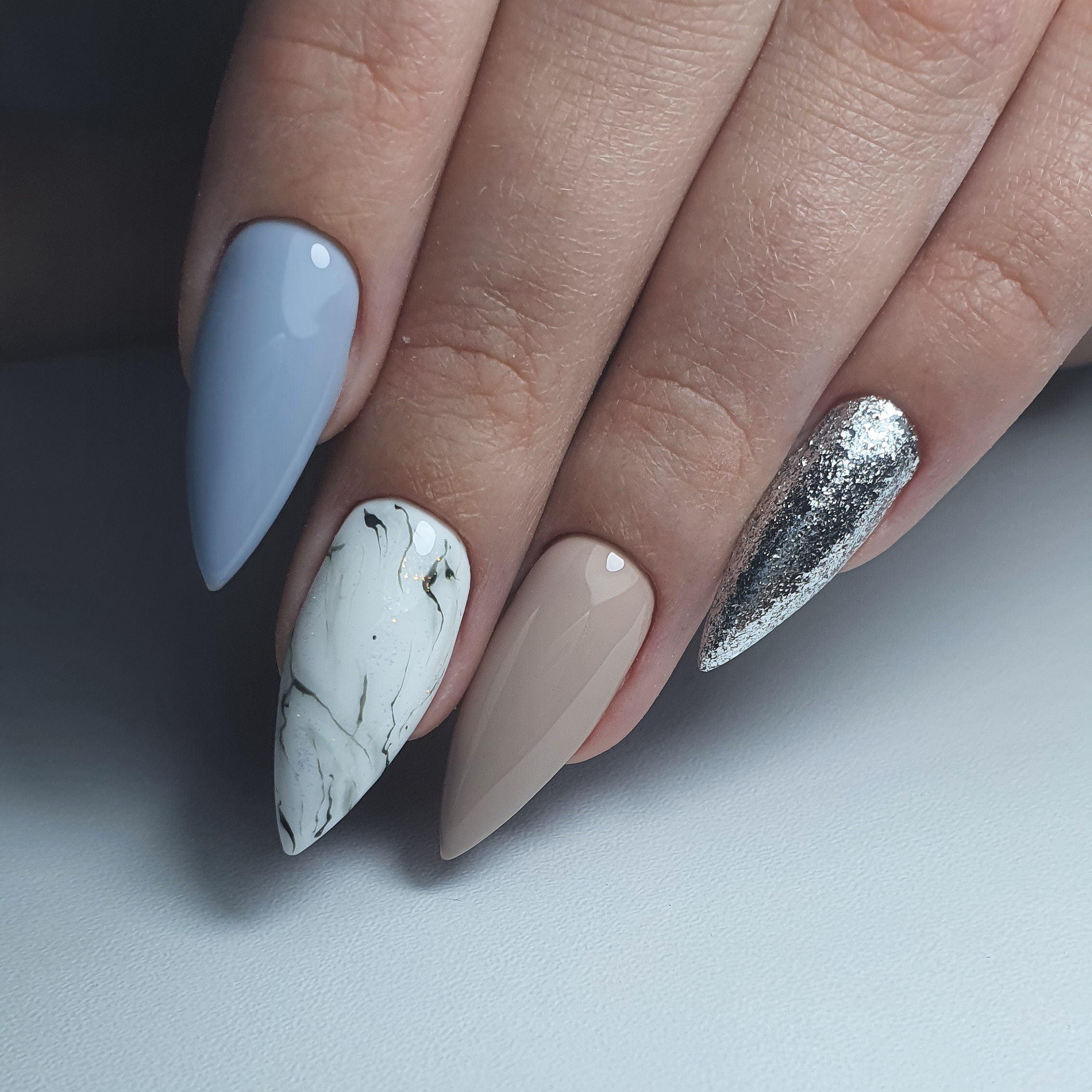 Маникюр с мраморным дизайном и серебряными блестками в пастельных тонах на длинные ногти.