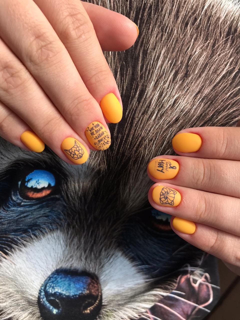 Матовый маникюр со слайдерами и надписями в оранжевом цвете на короткие ногти.