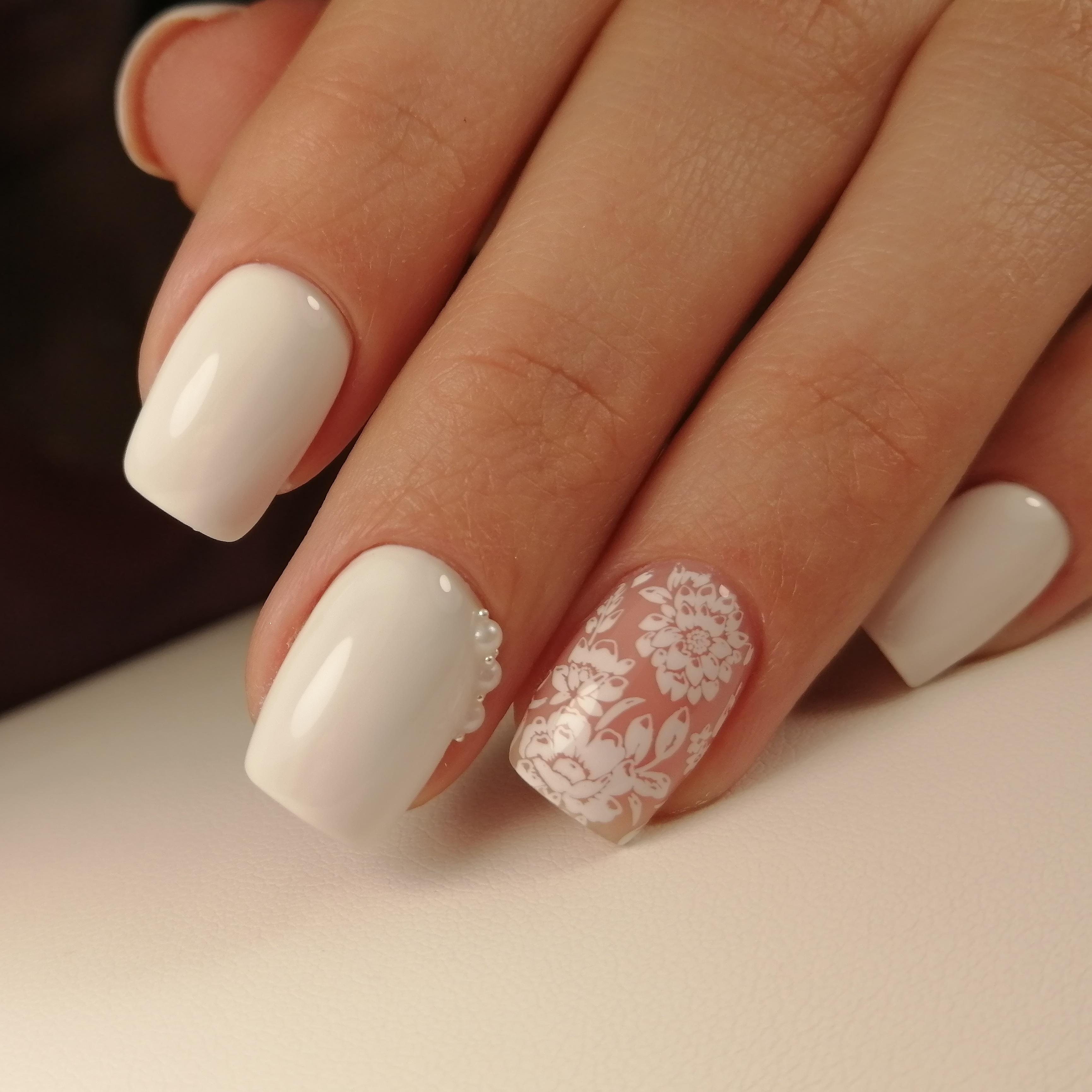Маникюр с цветочным стемпингом и стразами в молочном цвете на короткие ногти.