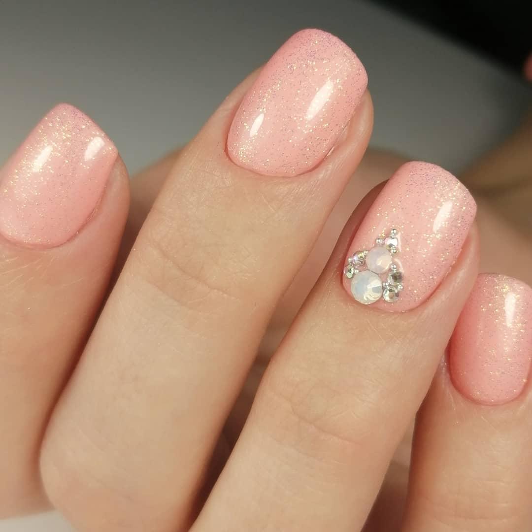 Маникюр с блестками и стразами в персиковом цвете на короткие ногти.
