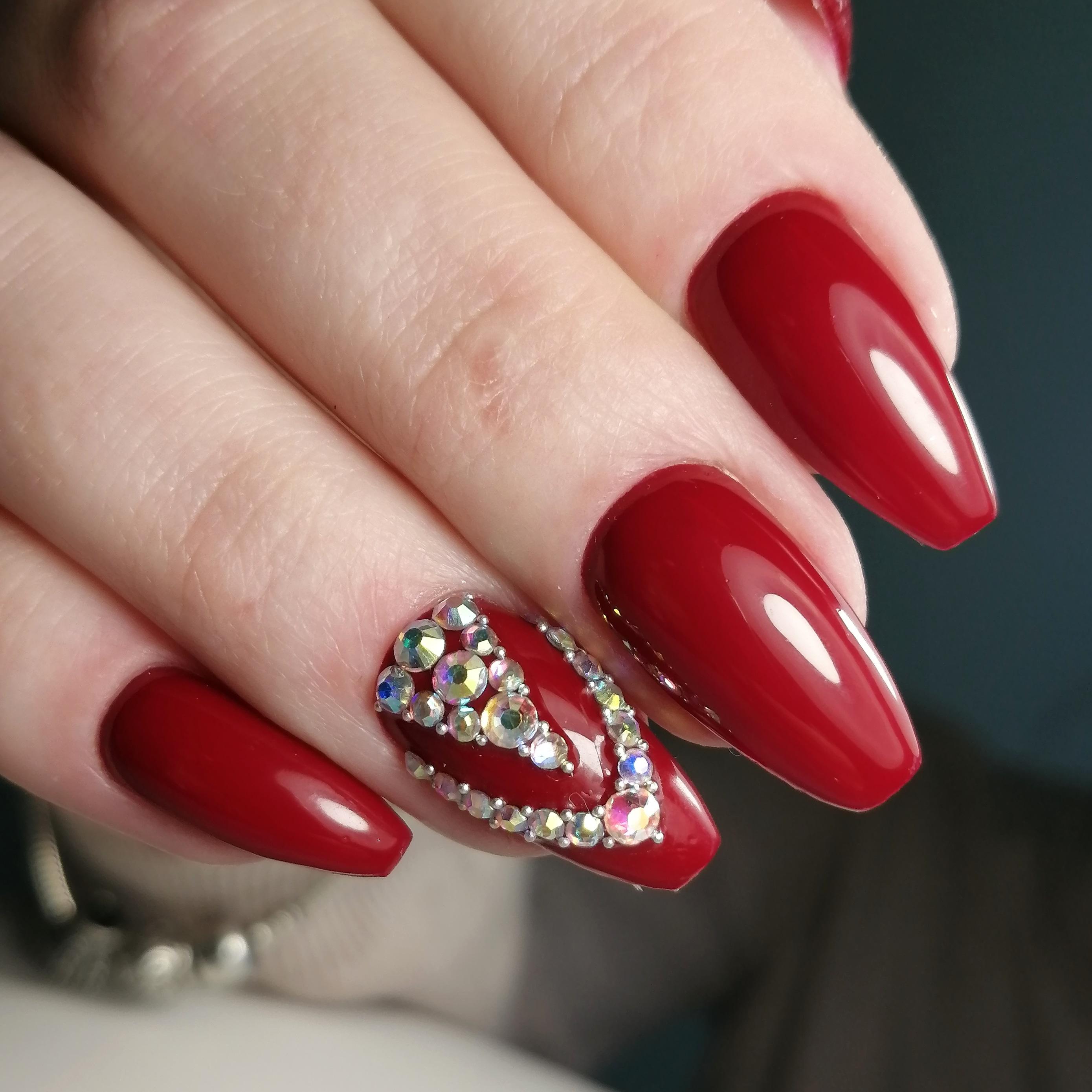 Маникюр со стразами в темно-красном цвете на длинные ногти.