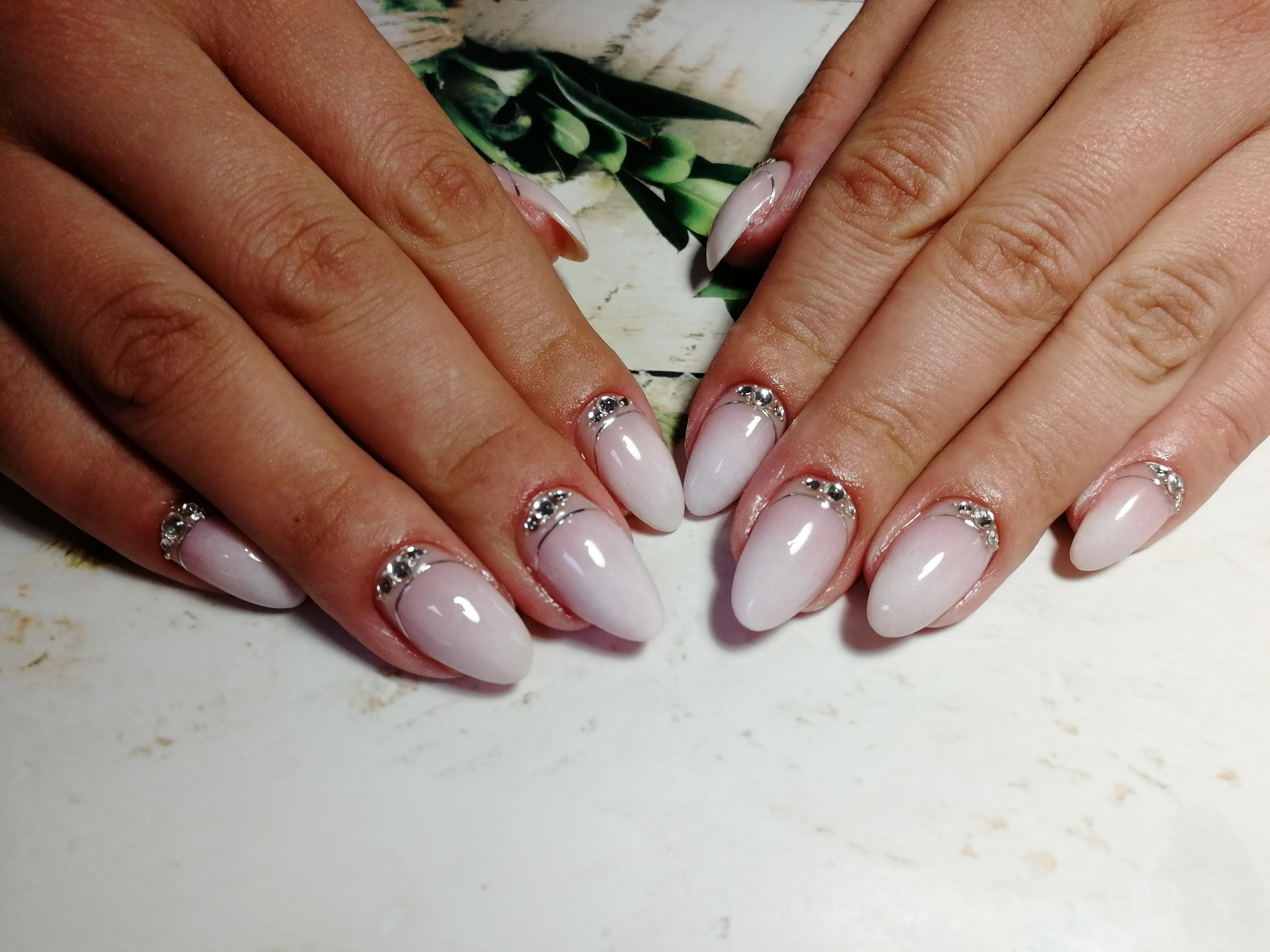 Лунный маникюр со стразами и серебряными полосками в молочном цвете на длинные ногти.