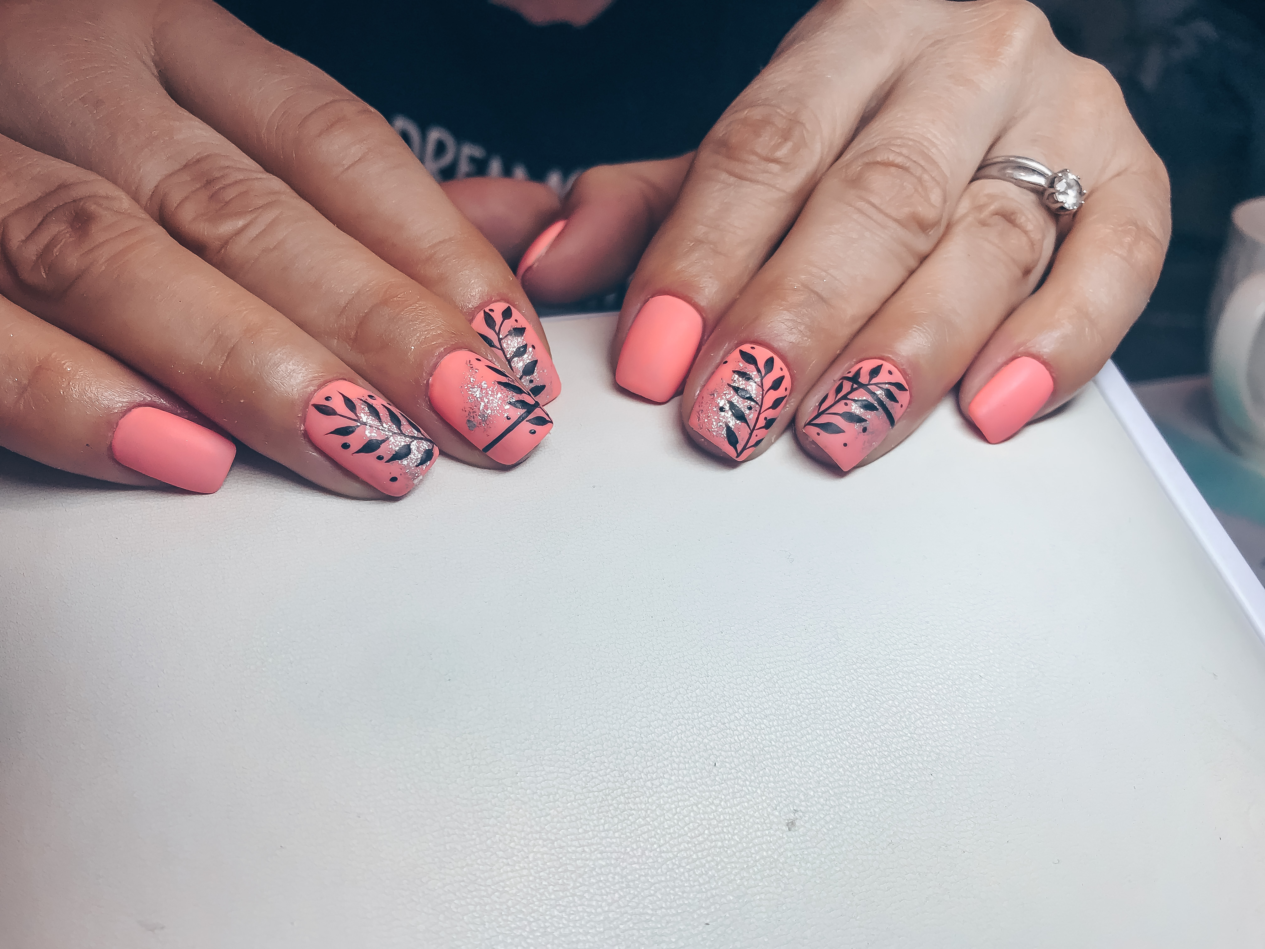 Матовый маникюр с растительными рисунками и серебряной фольгой в розовом цвете на короткие ногти.