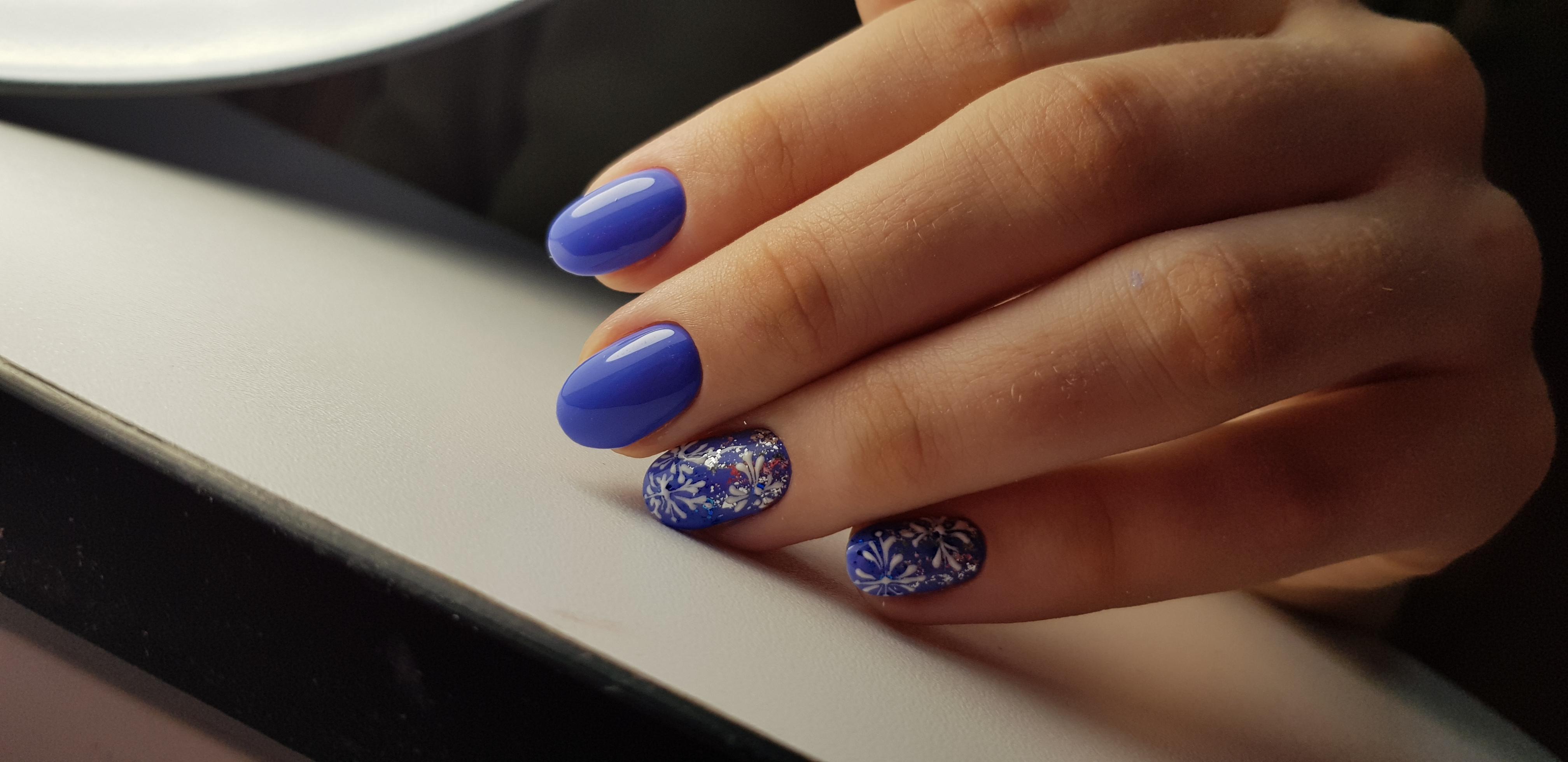 """Однотонный маникюр в синем цвете с белыми рисунками """"снежинки"""" и цветными блёстками."""
