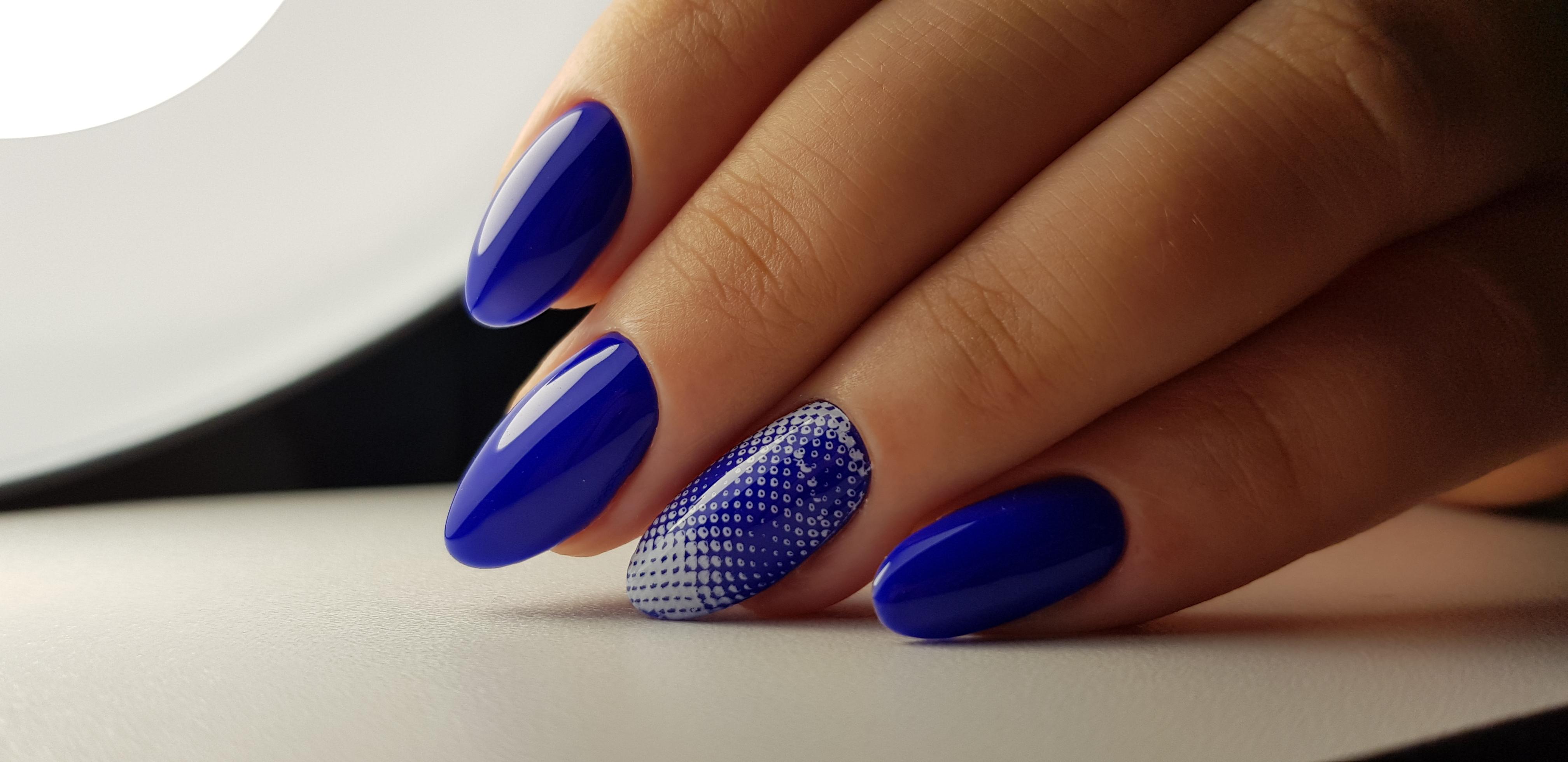 Однотонный маникюр в синем цвете с абстрактным рисунком.