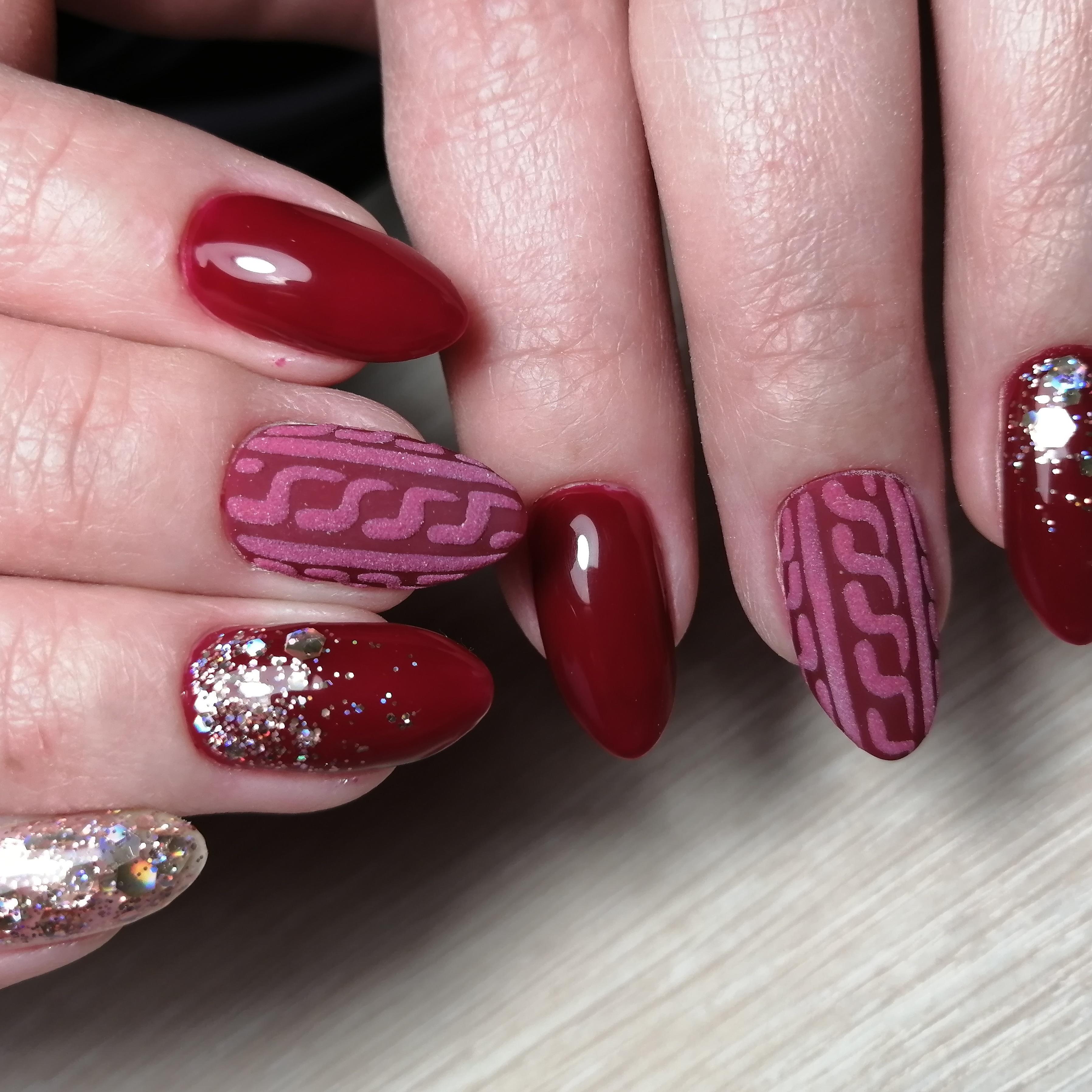 Маникюр в тёмно-красном цвете с песочным вязаным дизайном и серебряными блёстками.