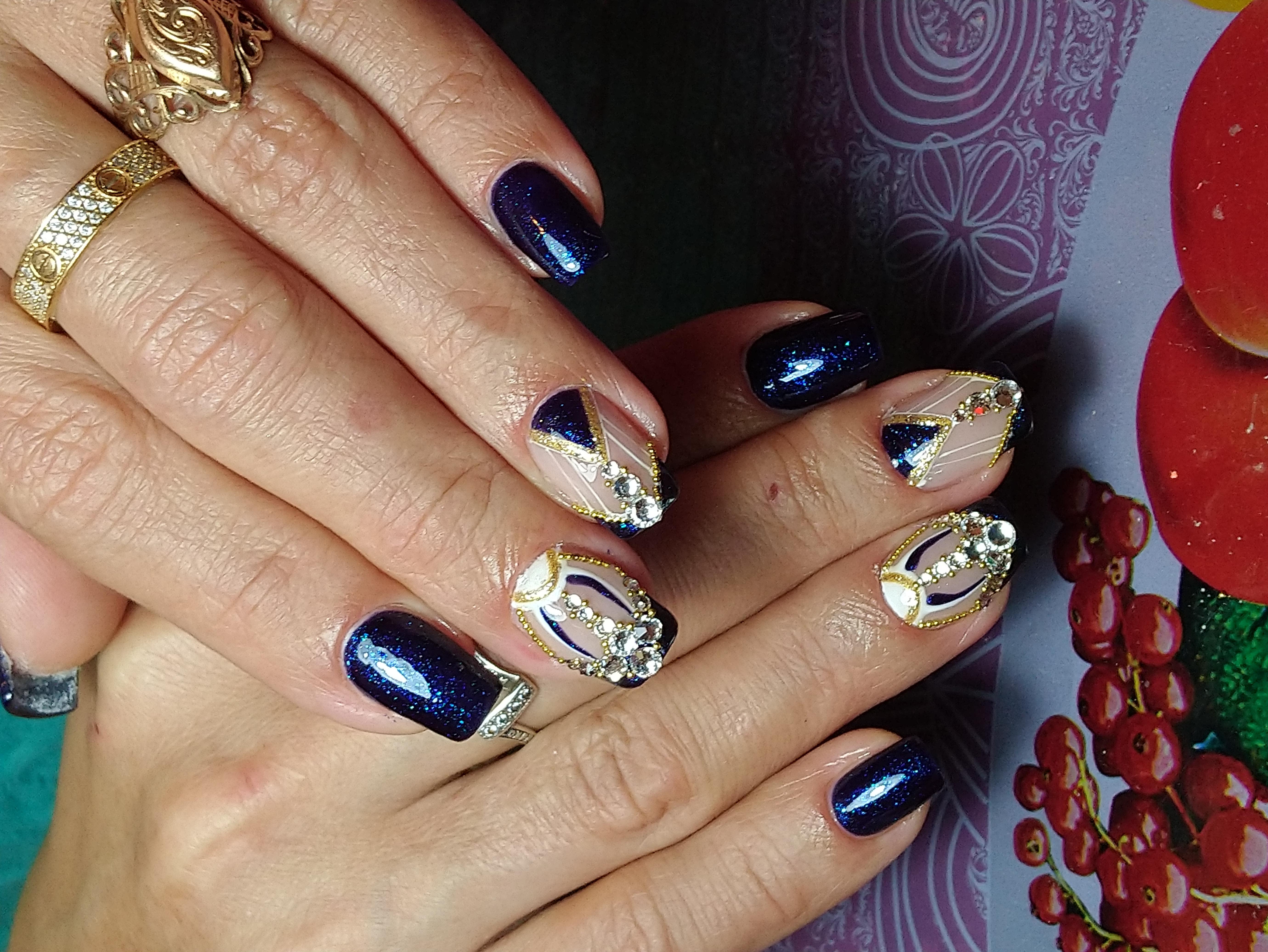 Маникюр в тёмно-синем цвете с нюдовым дизайном, геометрическим рисунком и стразами.