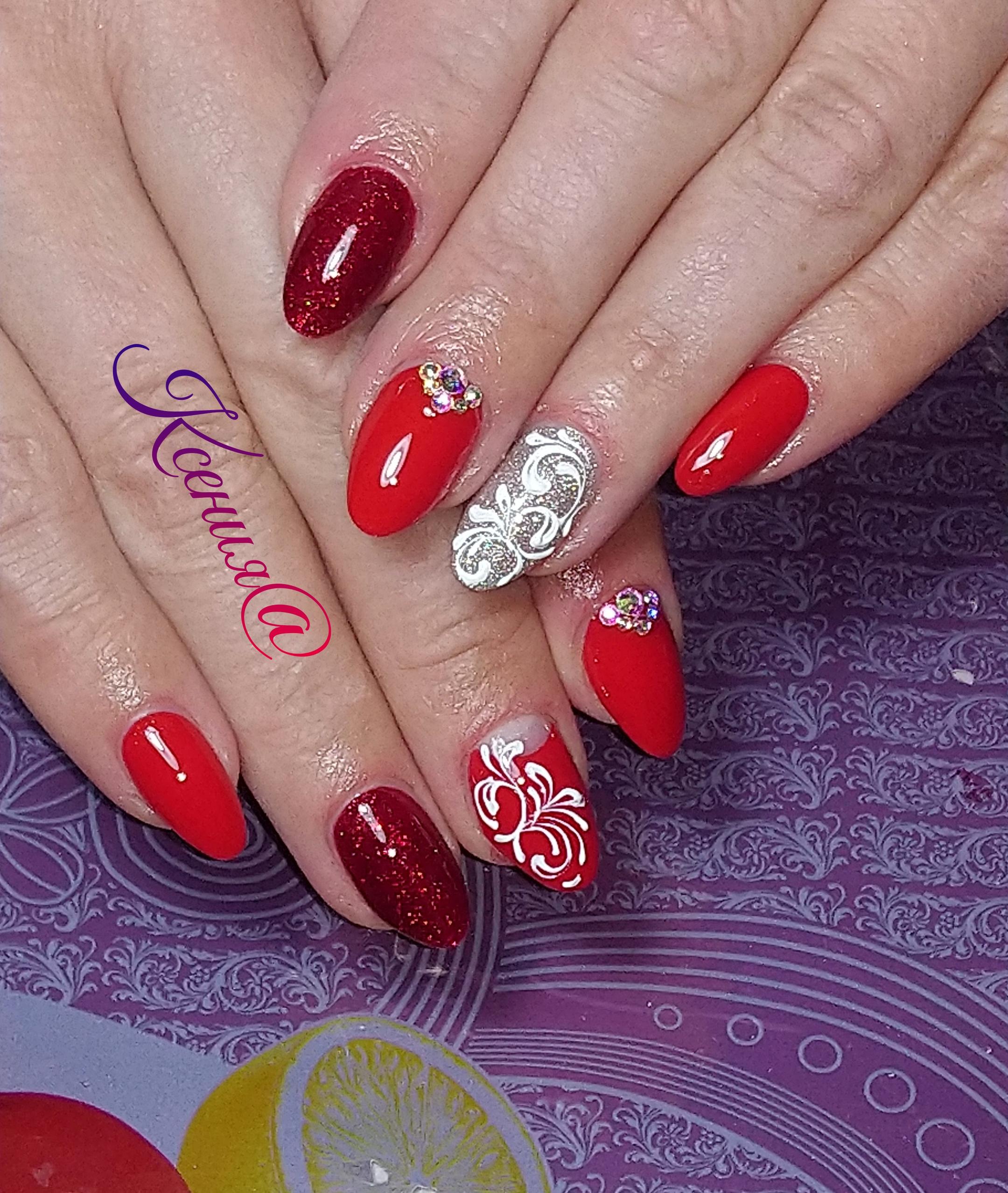 Маникюр в красном цвете с блестящим тёмно-красным дизайном, серебряными блёстками, вензелями и стразами.