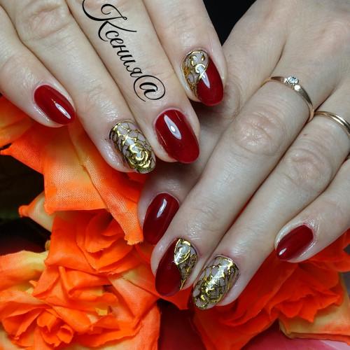 Огненно-красный маникюр дополнен золотым орнаментом.