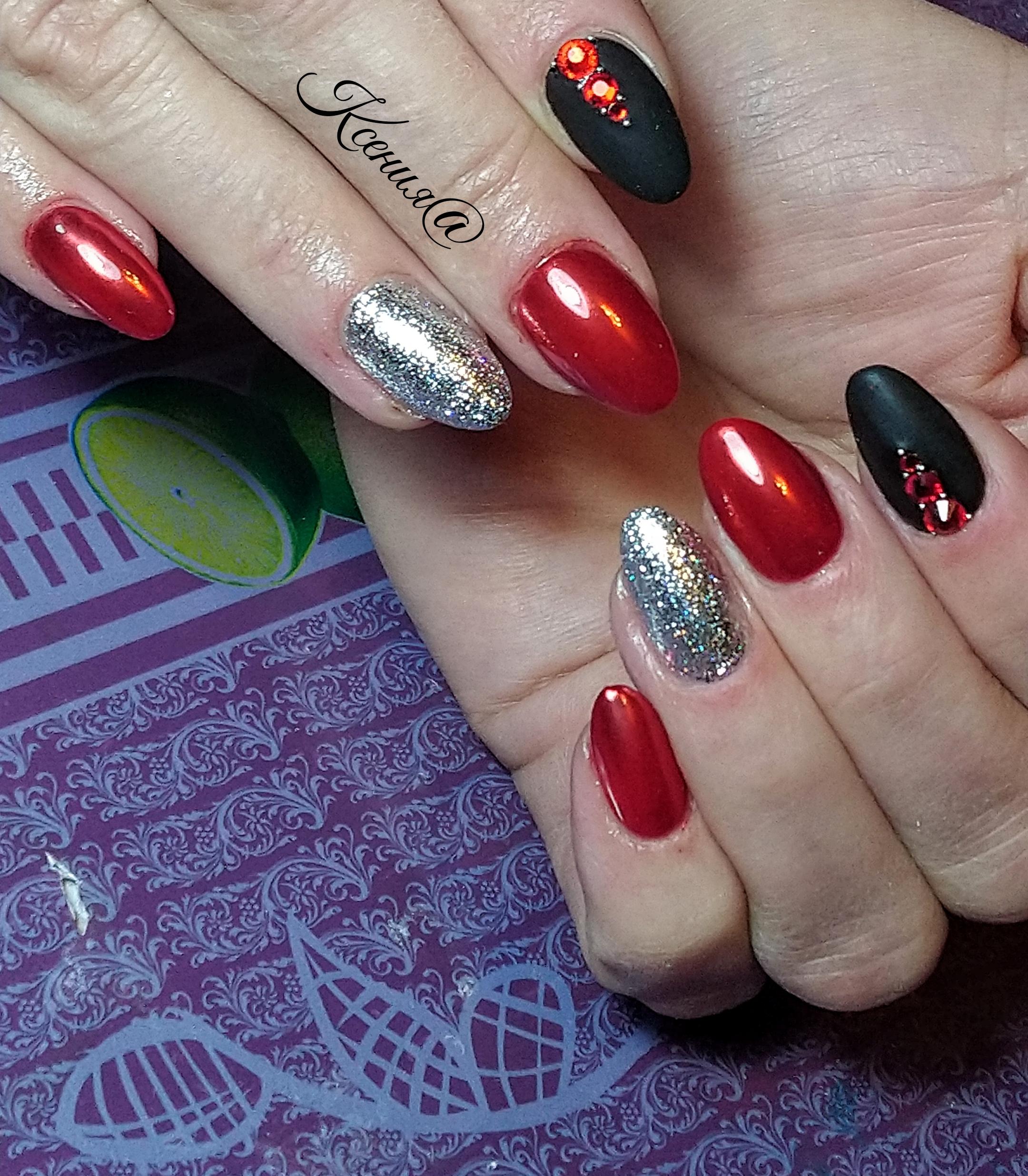 Маникюр в красном цвете с чёрным матовым дизайном, серебряными блёстками и стразами.