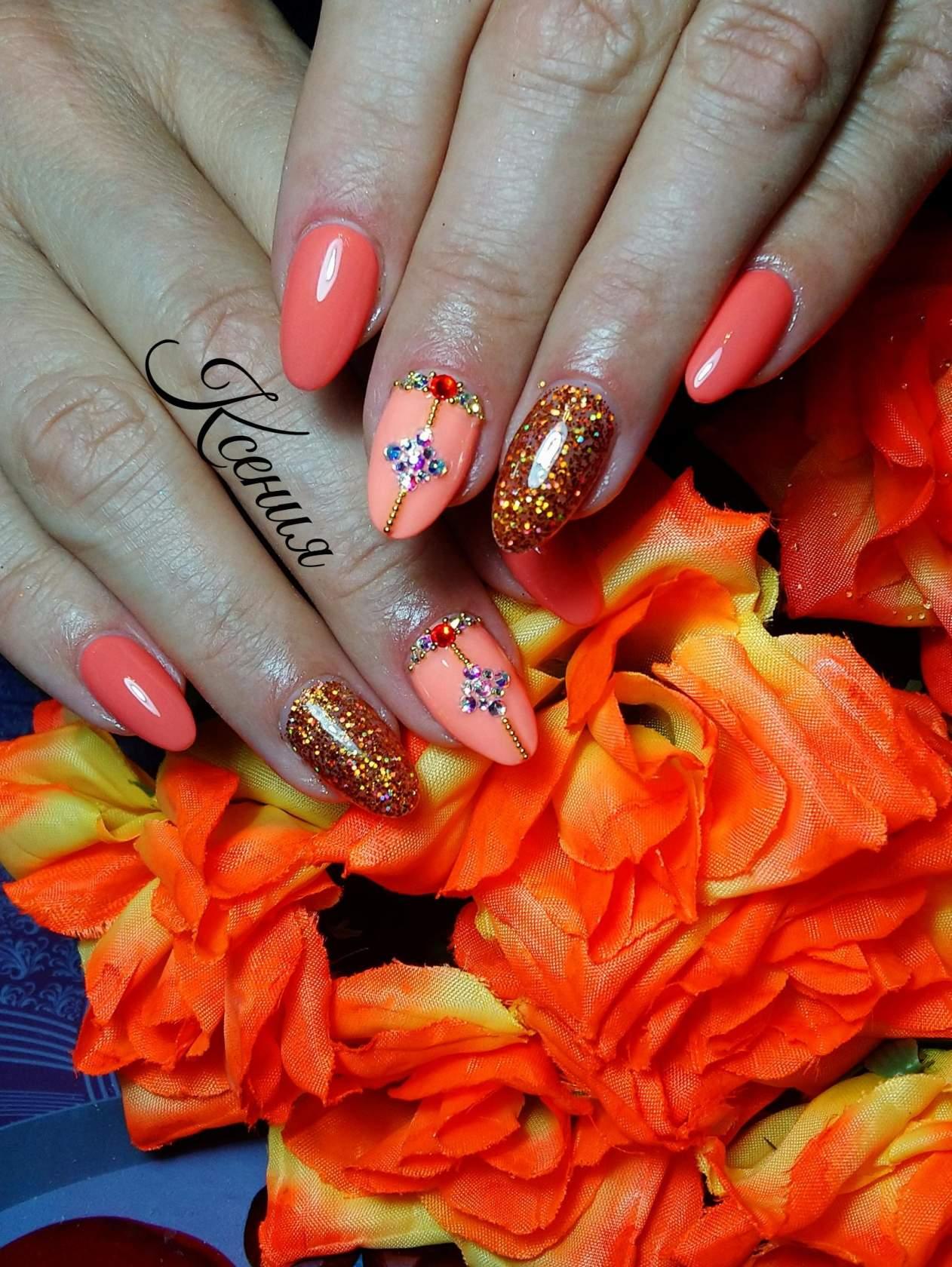 Маникюр в оранжевом цвете с персиковым дизайном, золотыми блёстками и стразами.