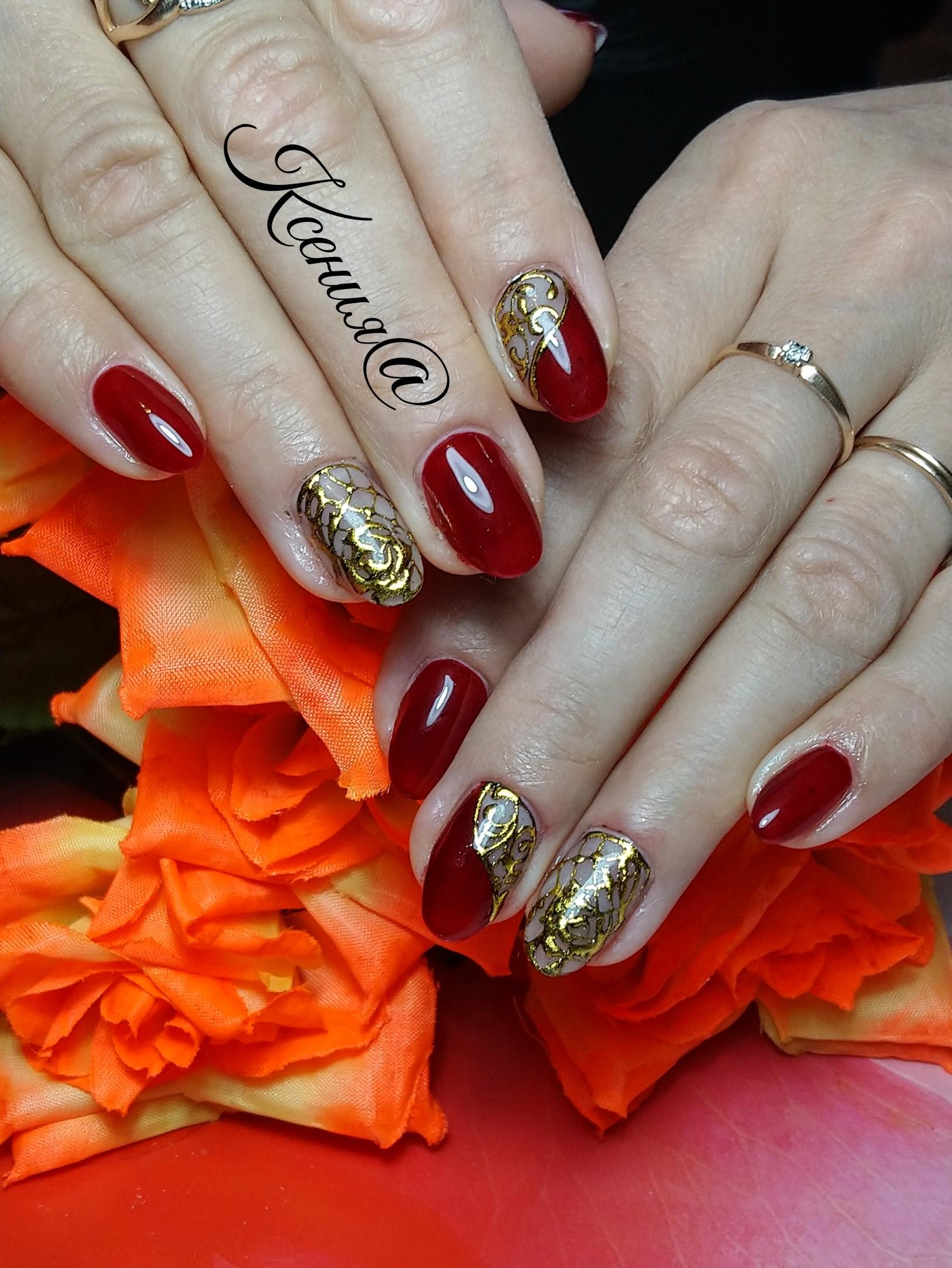 Маникюр в тёмно-красном цвете с золотым кружевным дизайном.