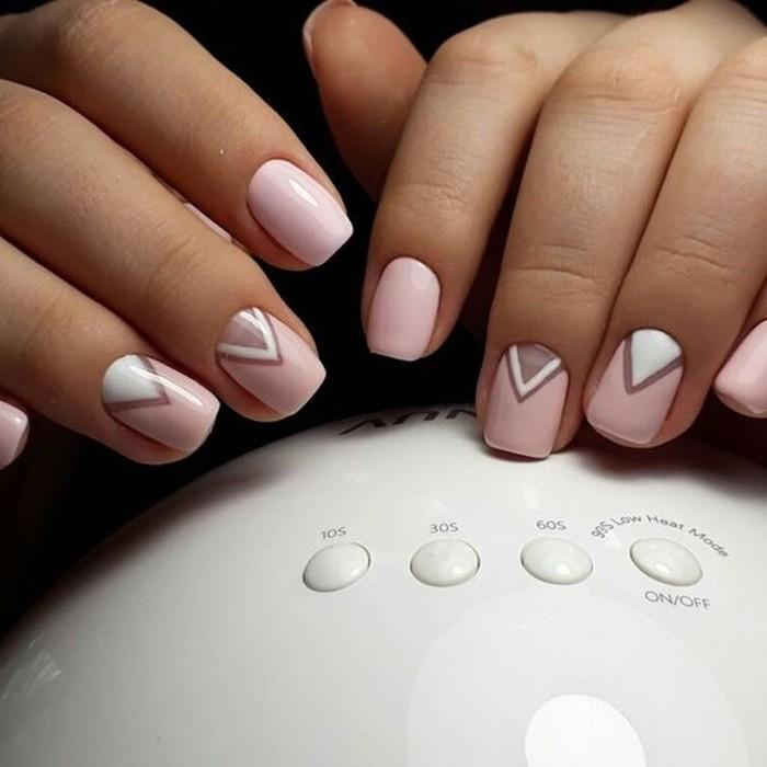 Маникюр в нежном розовом цвете с геометрическим дизайном.