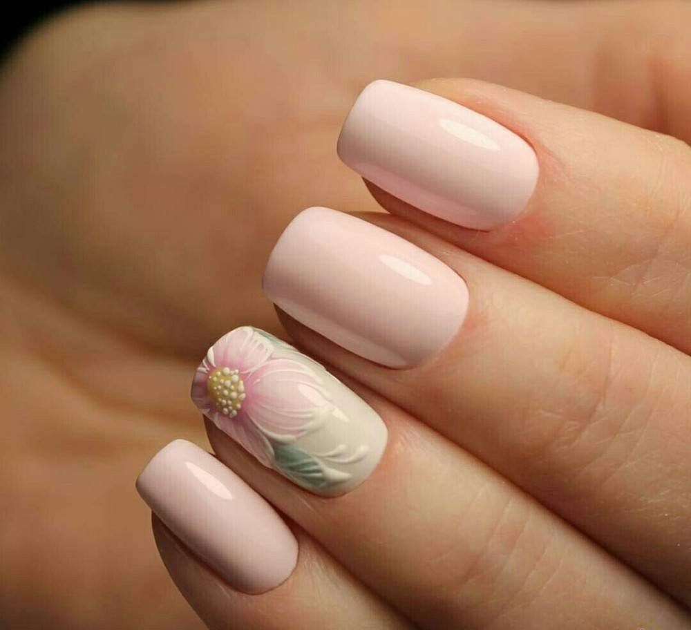 Маникюр в нежном розовом цвете с цветочным рисунком.