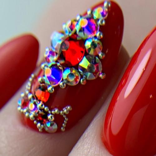 Яркий лак и крупные стразы на ногтях создают праздничное настроение.