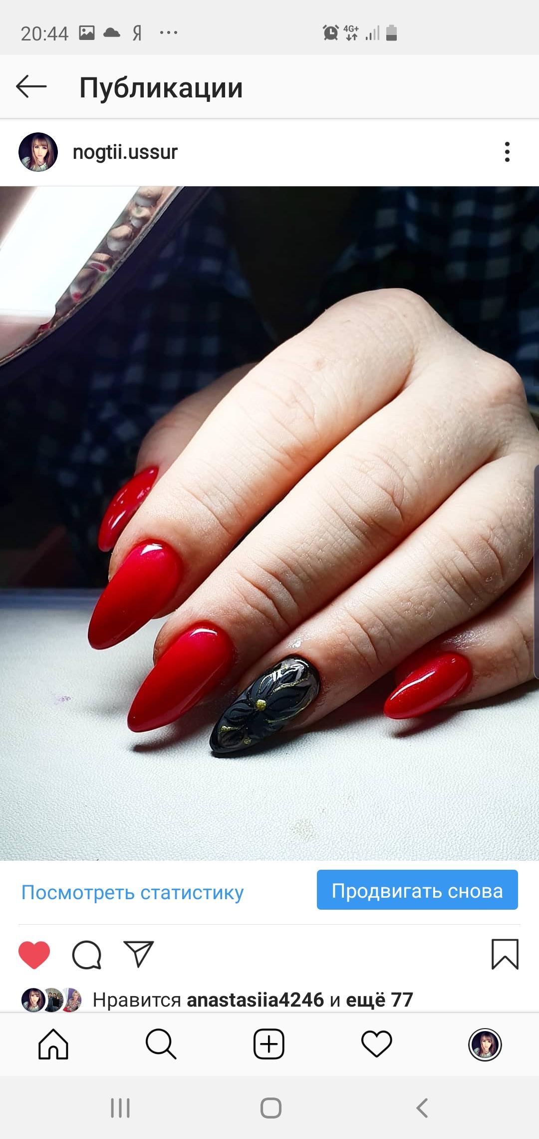 Маникюр в красном цвете с чёрным матовым цветочным дизайном и золотыми блёстками.