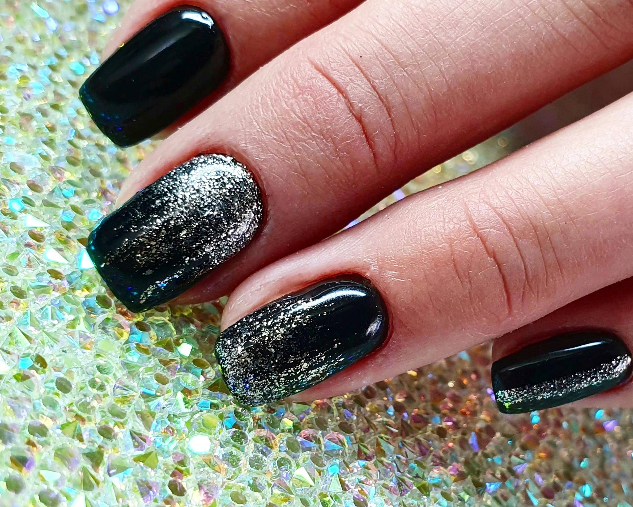 Маникюр в чёрном цвете с серебряными блёстками.