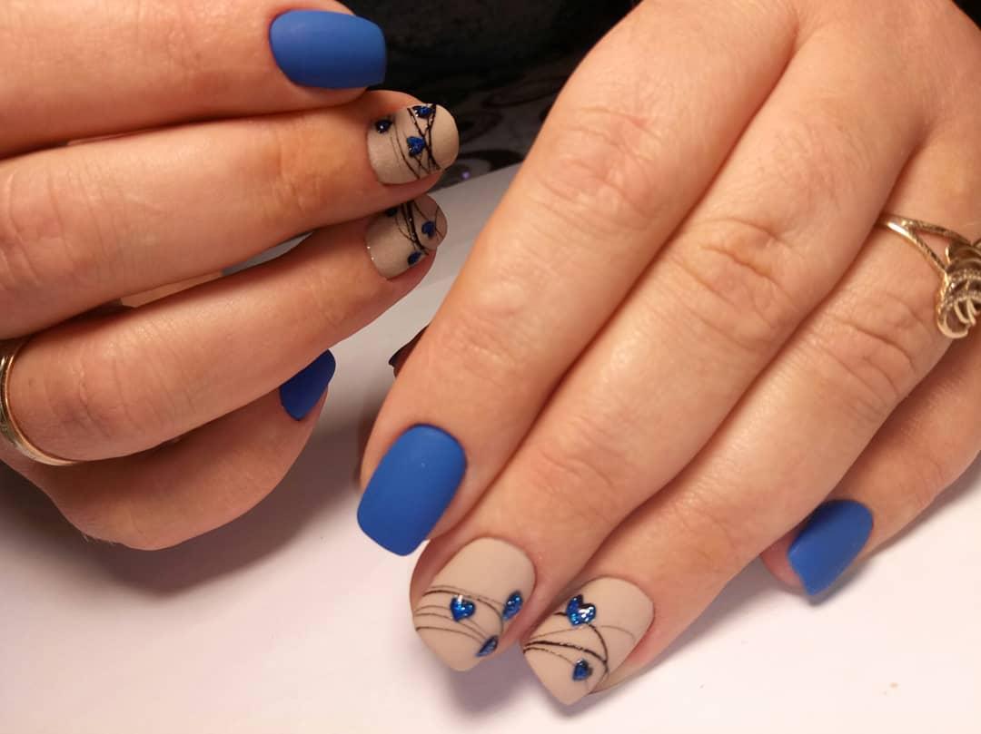 Матовый маникюр с нюдовым дизайном, сердечками и паутинкой в синем цвете.