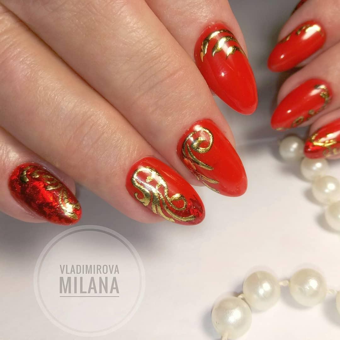 Маникюр с золотыми вензелями в красном цвете.