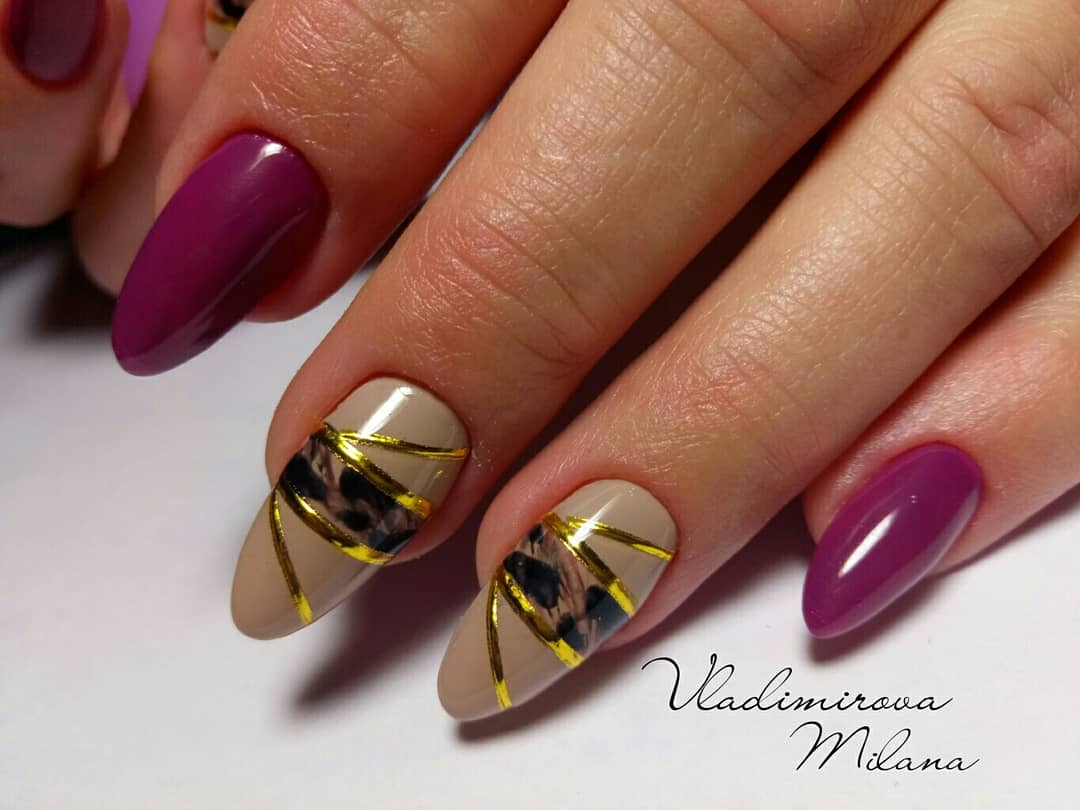 Маникюр с леопардовым принтом и золотыми полосками в баклажановом цвете.