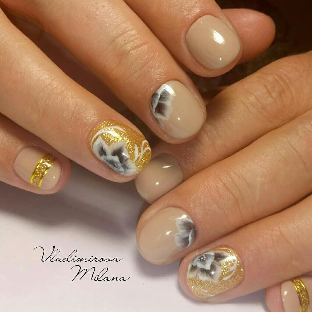 Маникюр с цветочным рисунком и золотыми блестками в бежевом цвете.