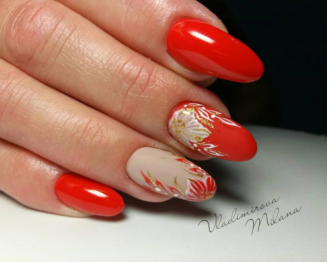 Маникюр с цветочным рисунком и золотыми блестками в красном цвете.