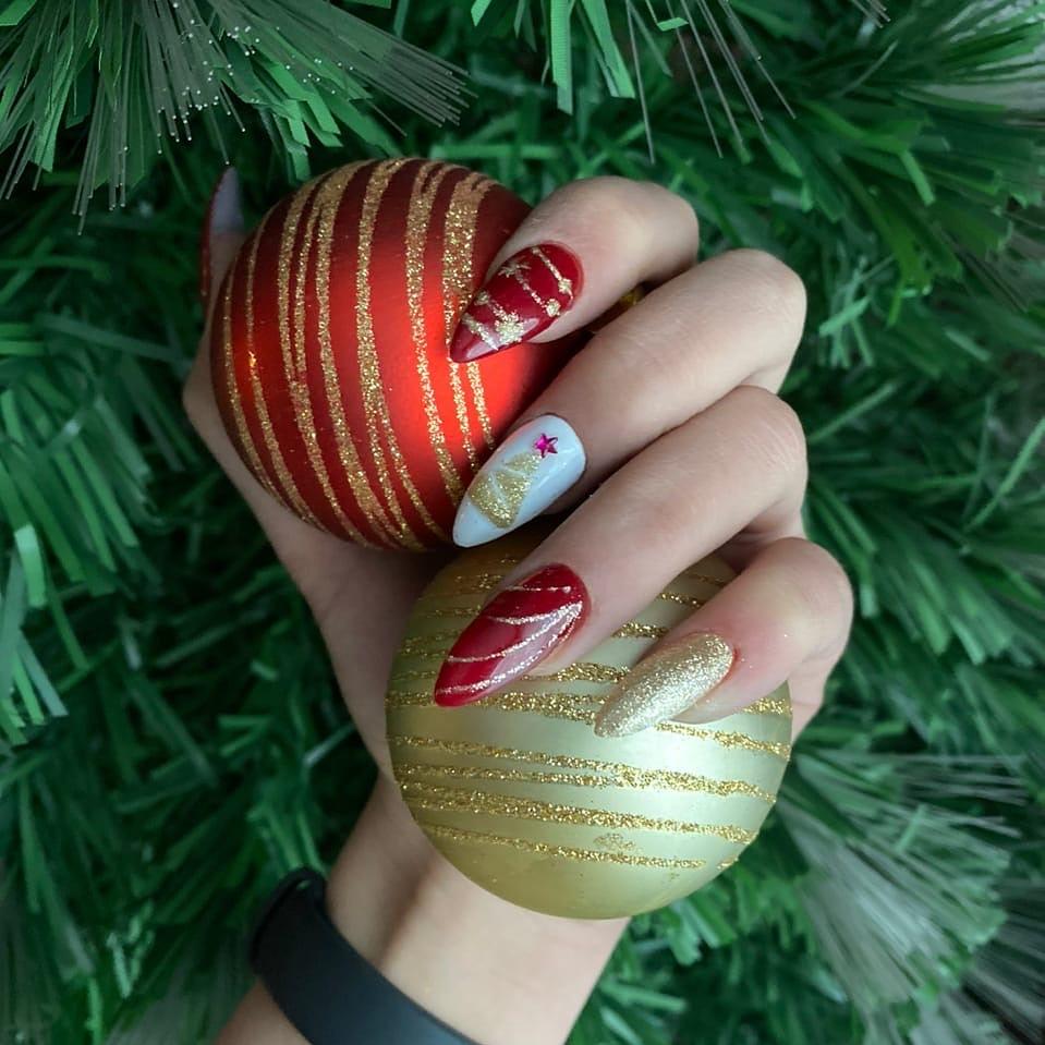 Праздничный глянцевый маникюр в красном цвете с контрастным дизайном, золотыми блёстками и новогодними рисунками.