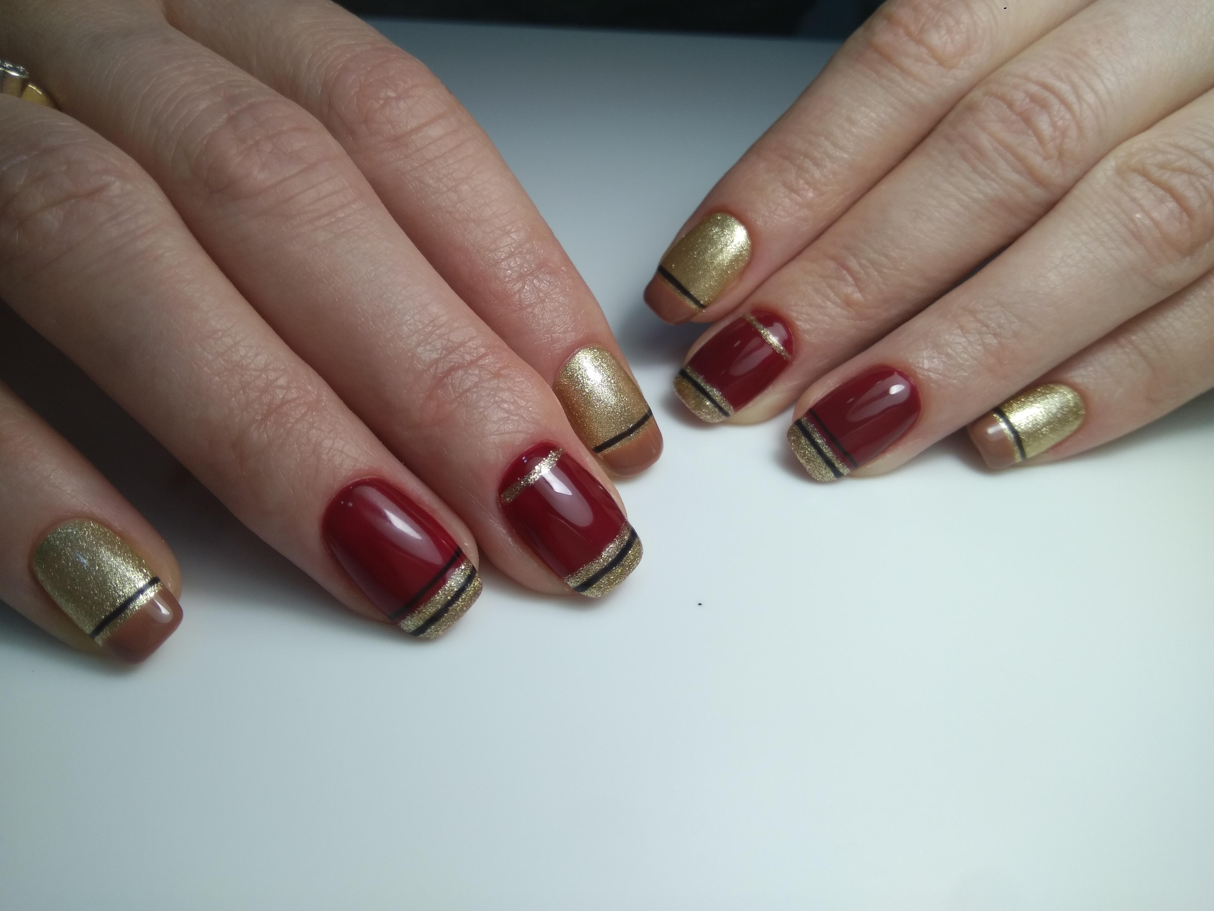 Блестящий золотой маникюр с тёмно-красным дизайном и полосками.