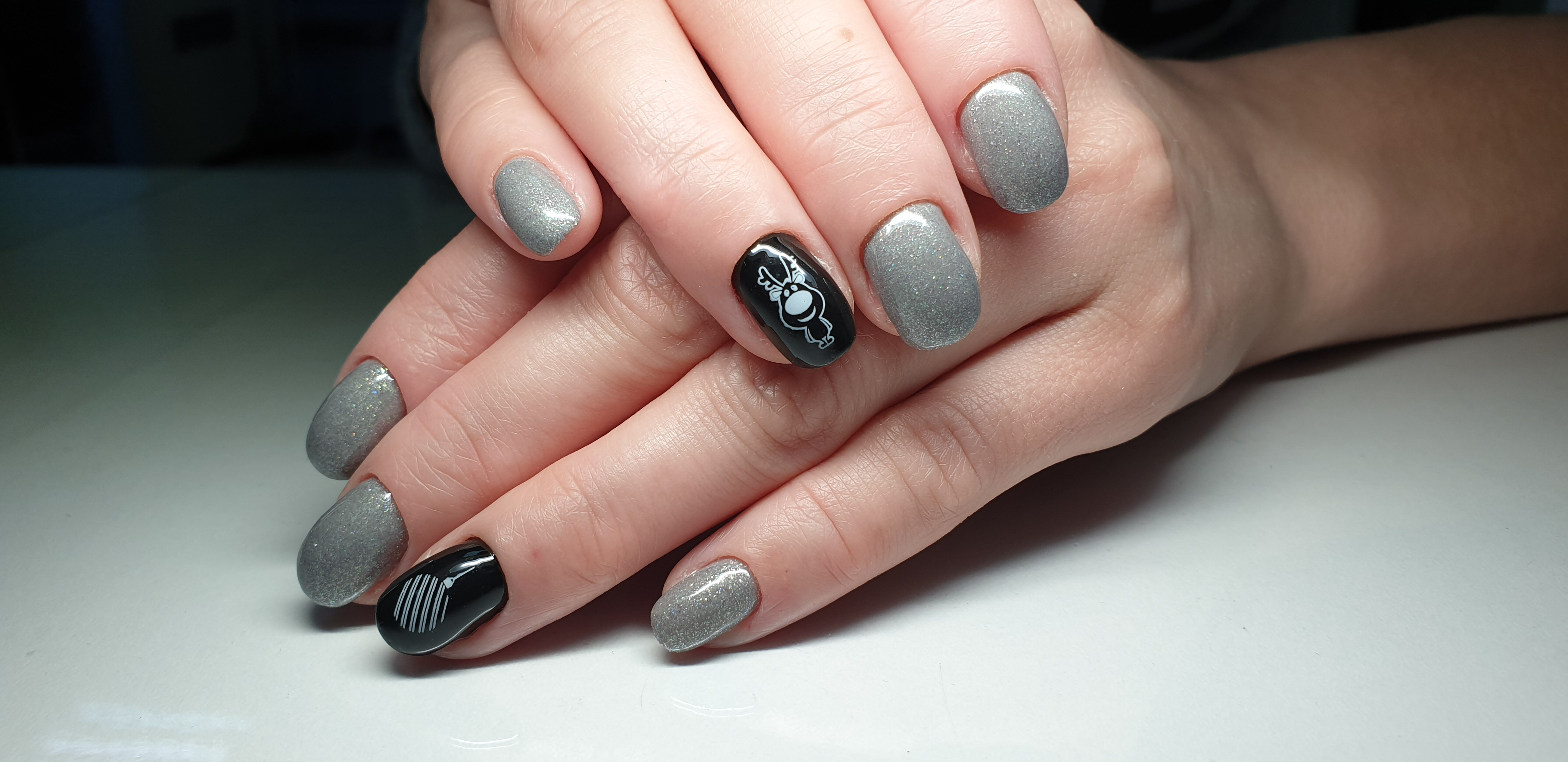 Однотонный маникюр в серебряном цвете с чёрным дизайном и новогодними слайдерами.
