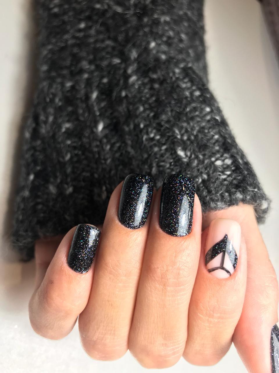 Маникюр в чёрном цвете с абстрактным рисунком и блёстками.
