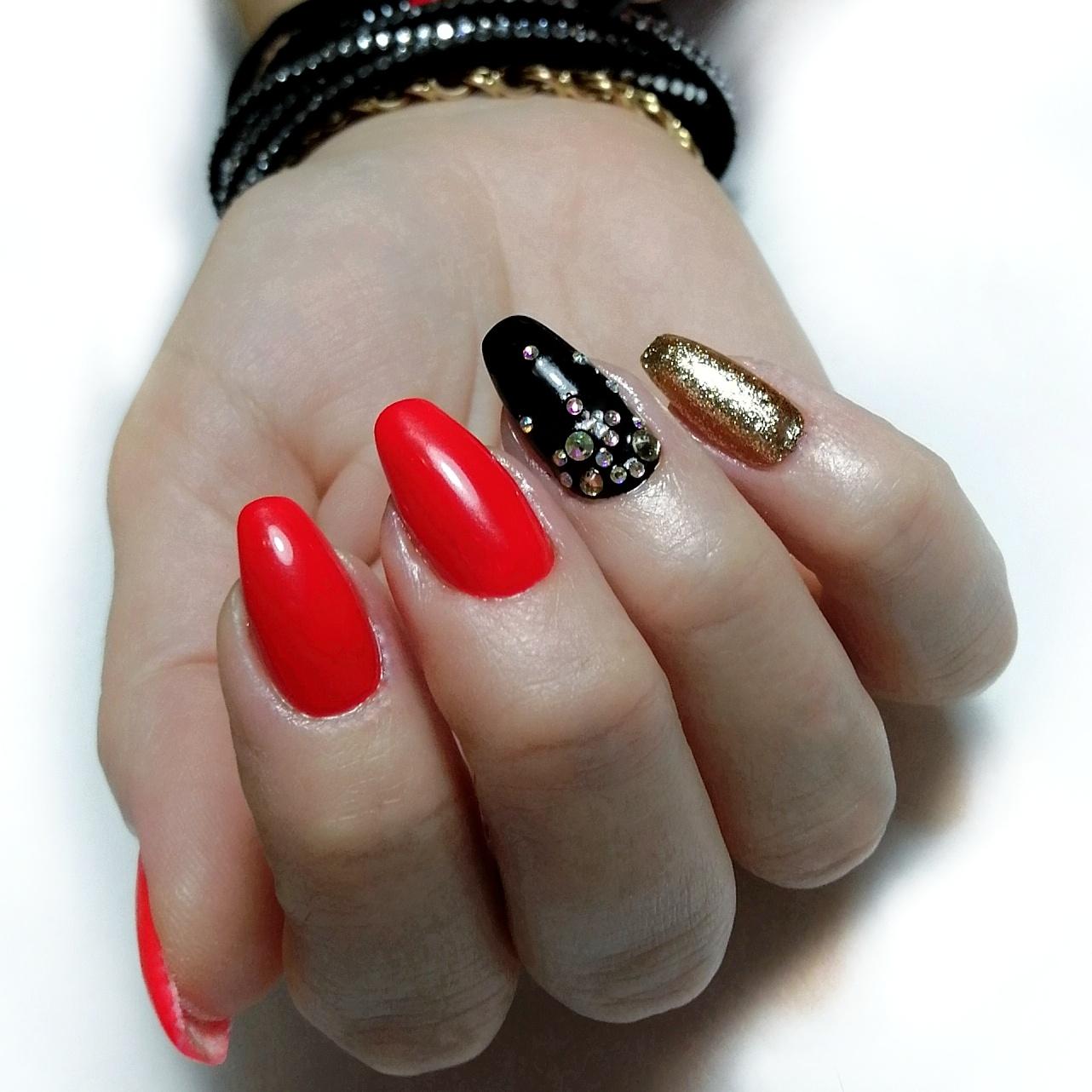 Маникюр в красном цвете с чёрным дизайном, золотыми блёстками и стразами.