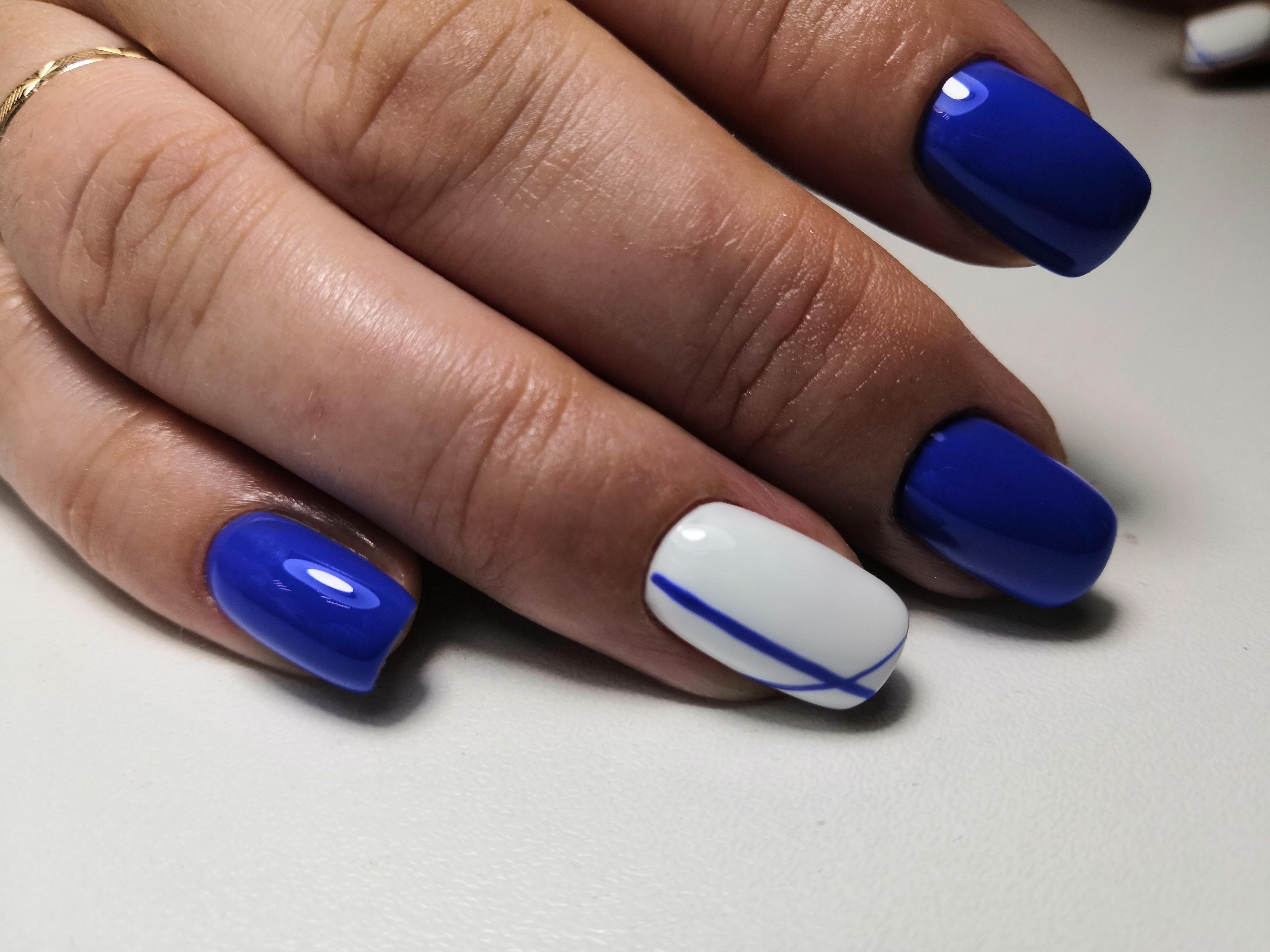 Маникюр в синем цвете с белым дизайном и синими полосками.