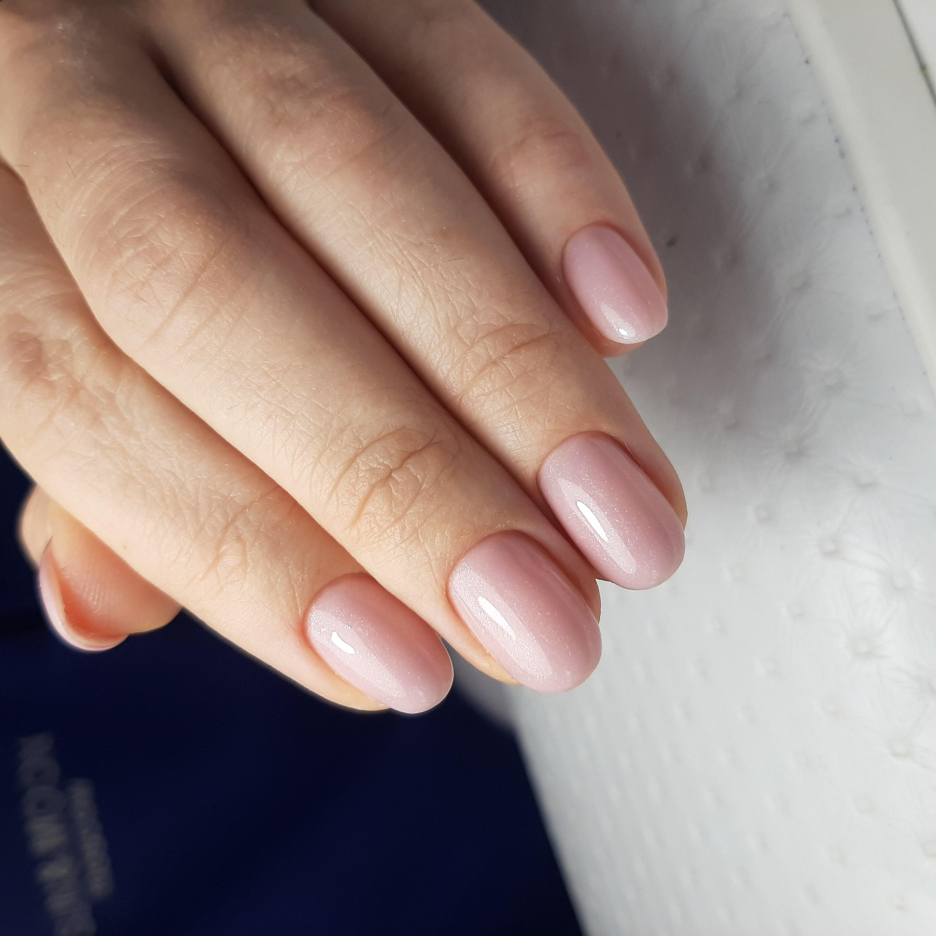 Нюдовый глянцевый однотонный маникюр в нежном розовом цвете.
