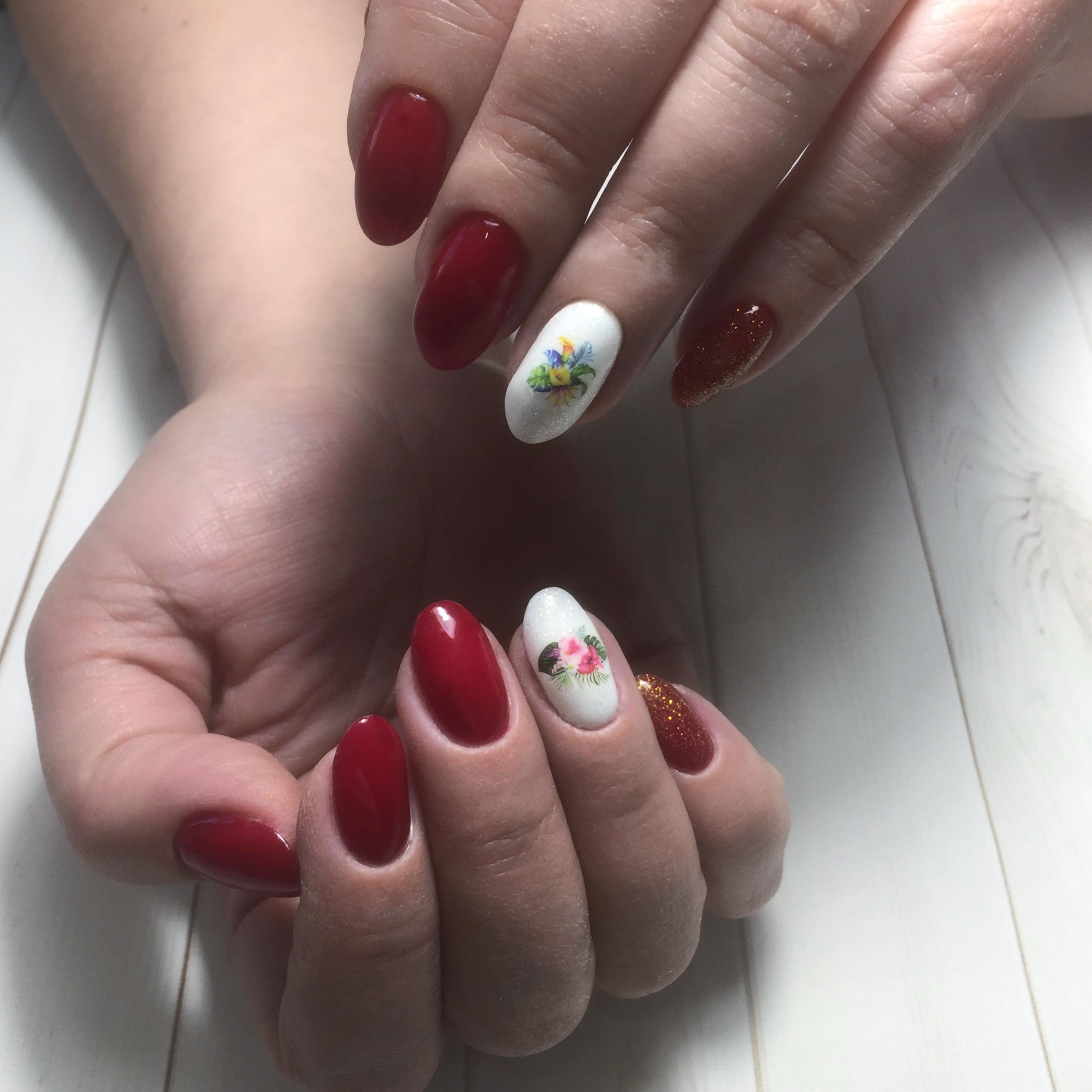 Маникюр с цветочными слайдерами и золотыми блестками в бордовом цвете.