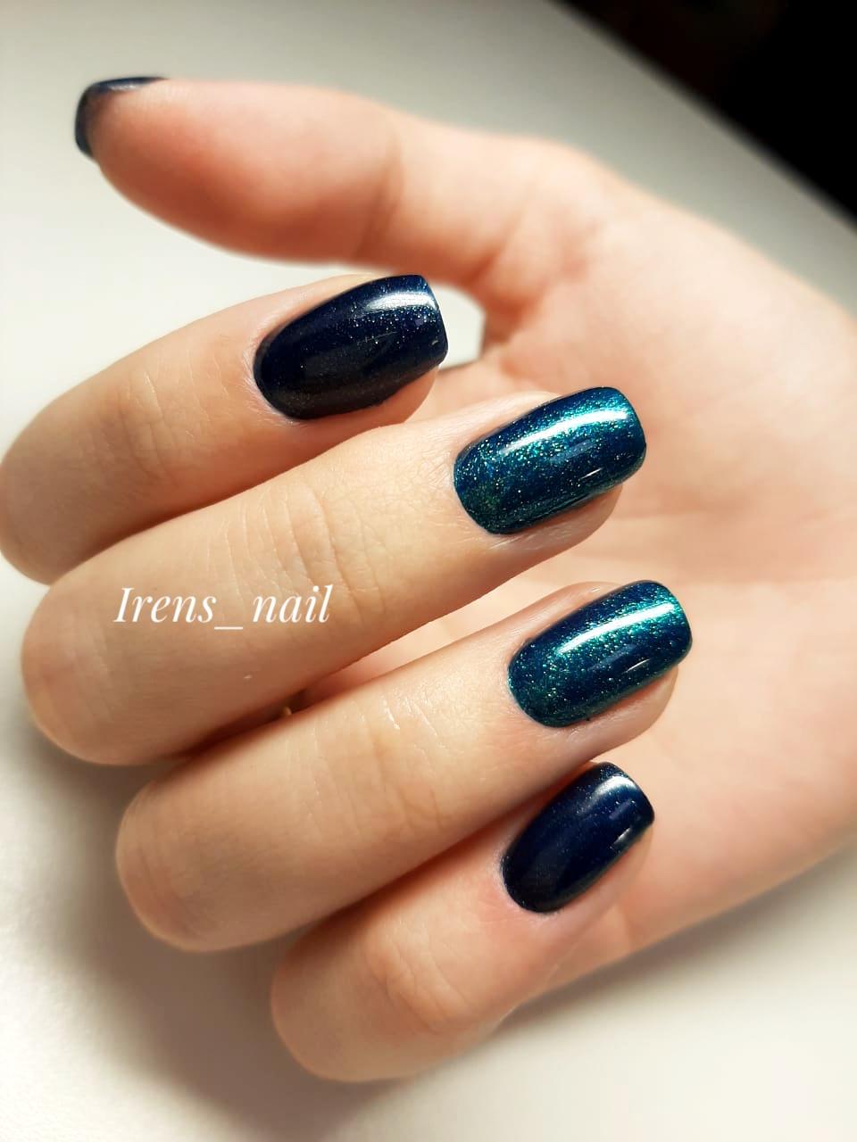Маникюр в тёмно-синем цвете с синими блёстками.