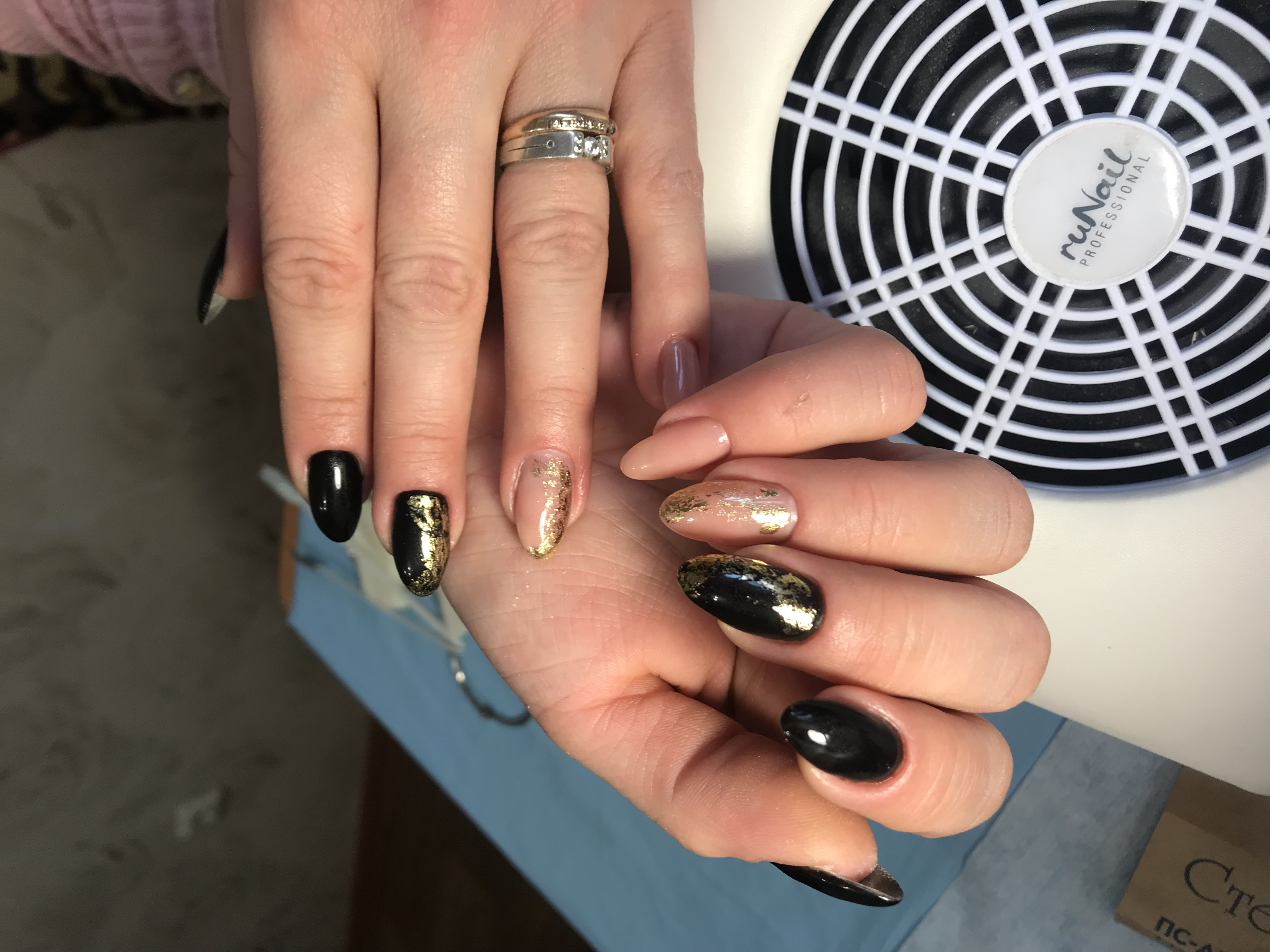 Маникюр в чёрном цвете с нюдовым дизайном и золотой фольгой.