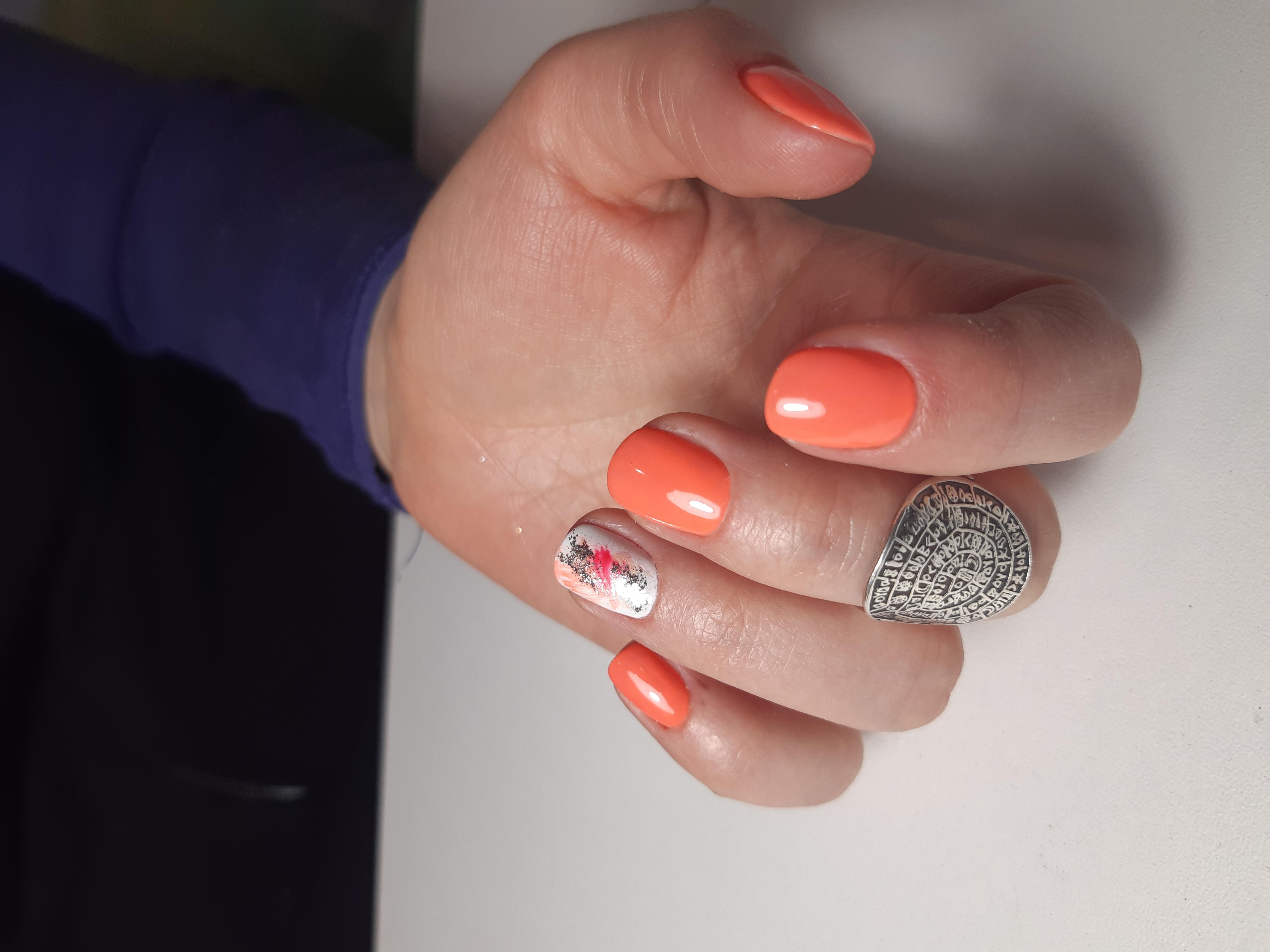 Маникюр в ярком оранжевом цвете с абстрактным дизайном и серебряными блёстками.