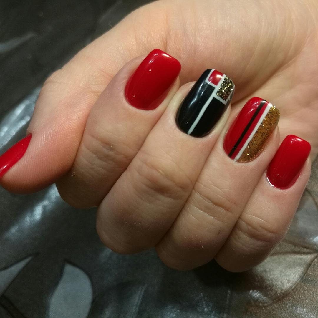 Маникюр в красном цвете с геометрическим дизайном и золотыми блёстками.