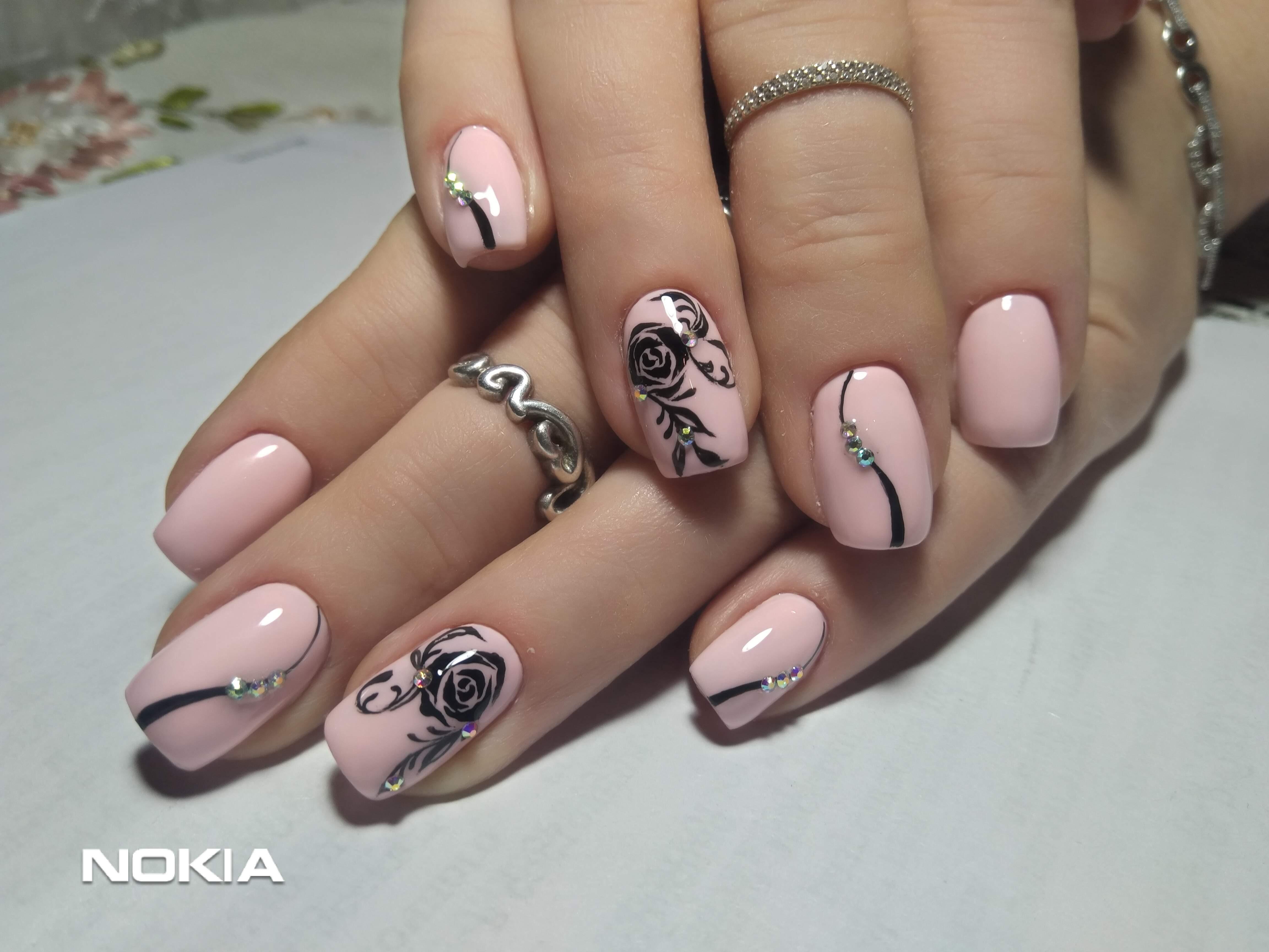 Маникюр в розовом цвете с цветочными рисунками, узорами и стразами.