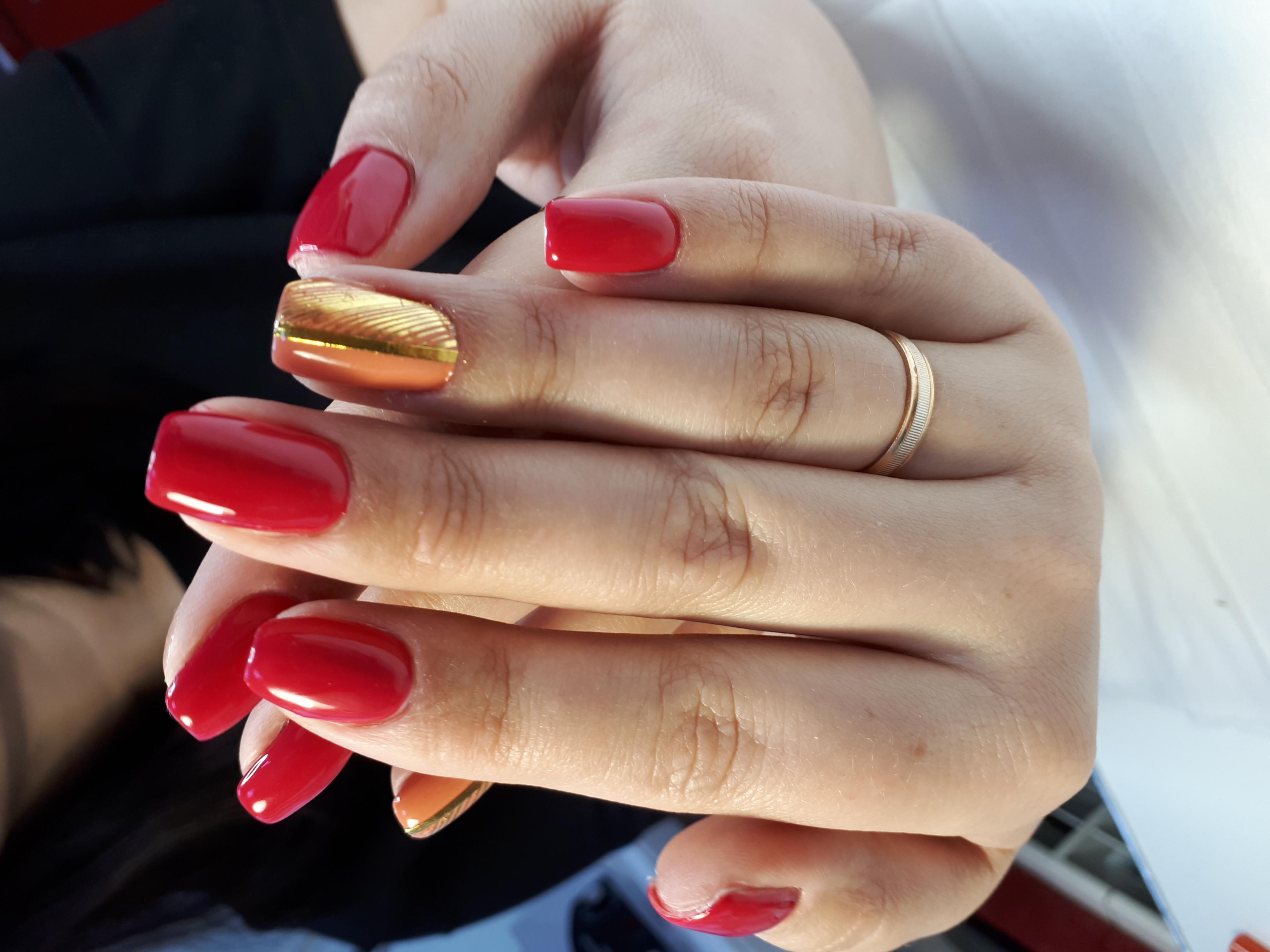 Однотонный маникюр в красном цвете с золотыми полосками.