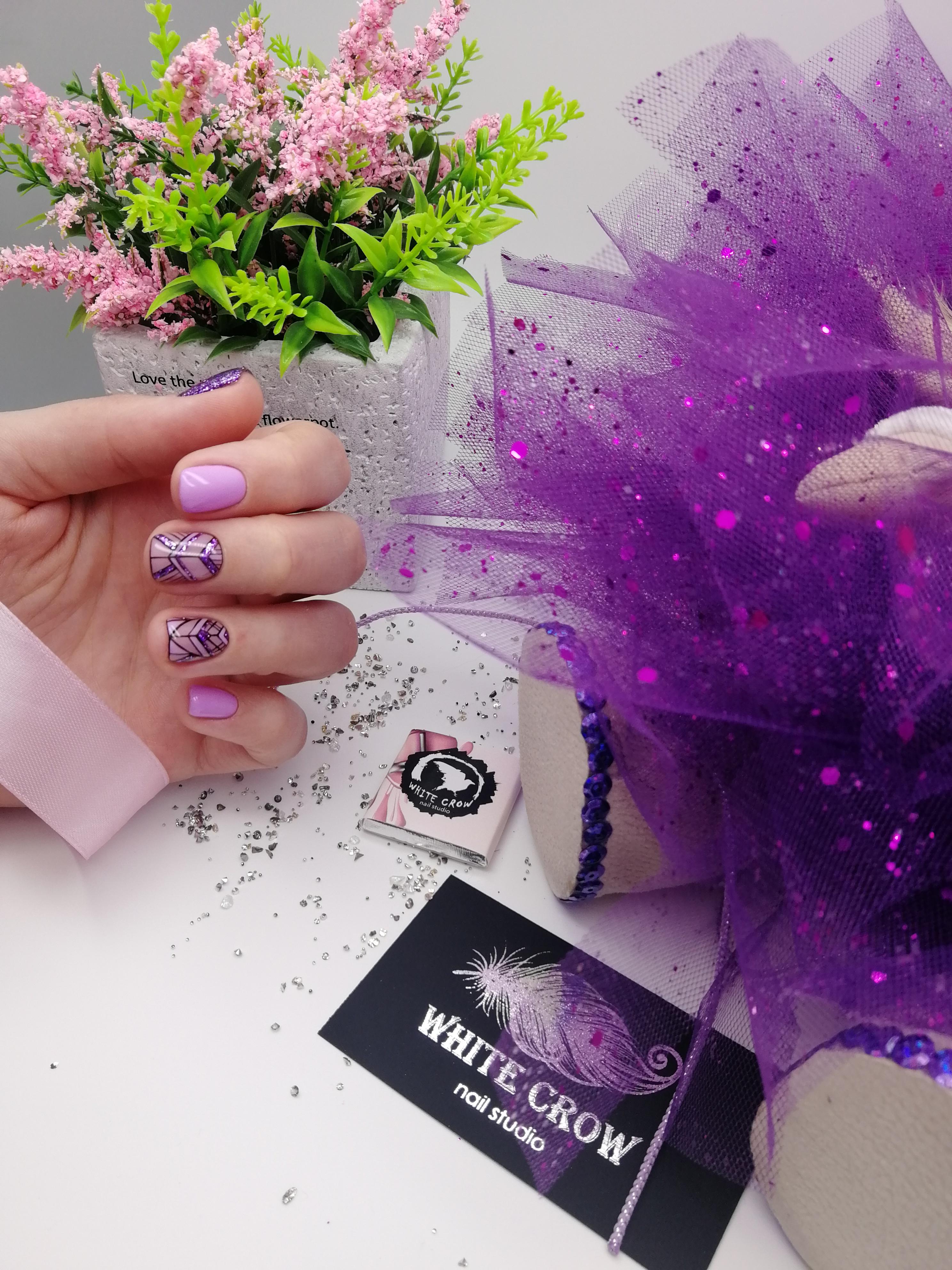 Маникюр в сиреневом цвете с геометрическим рисунком и фиолетовыми блёстками.