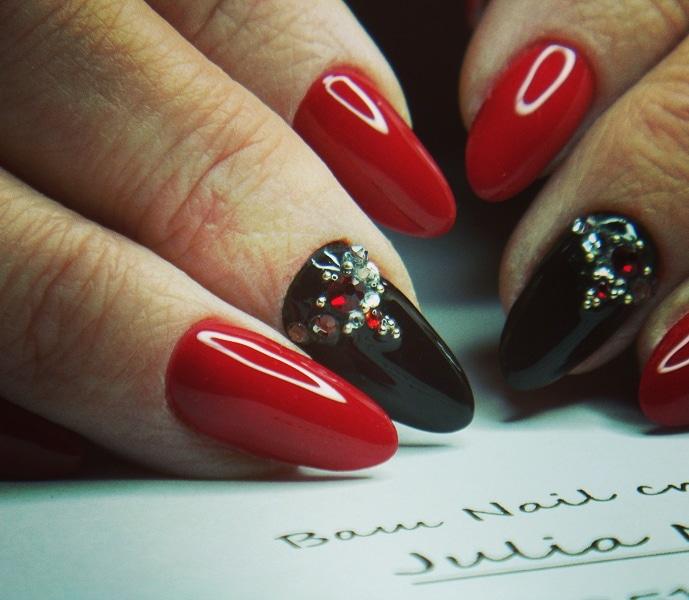 Маникюр в красном цвете с чёрным дизайном и цветными стразами.