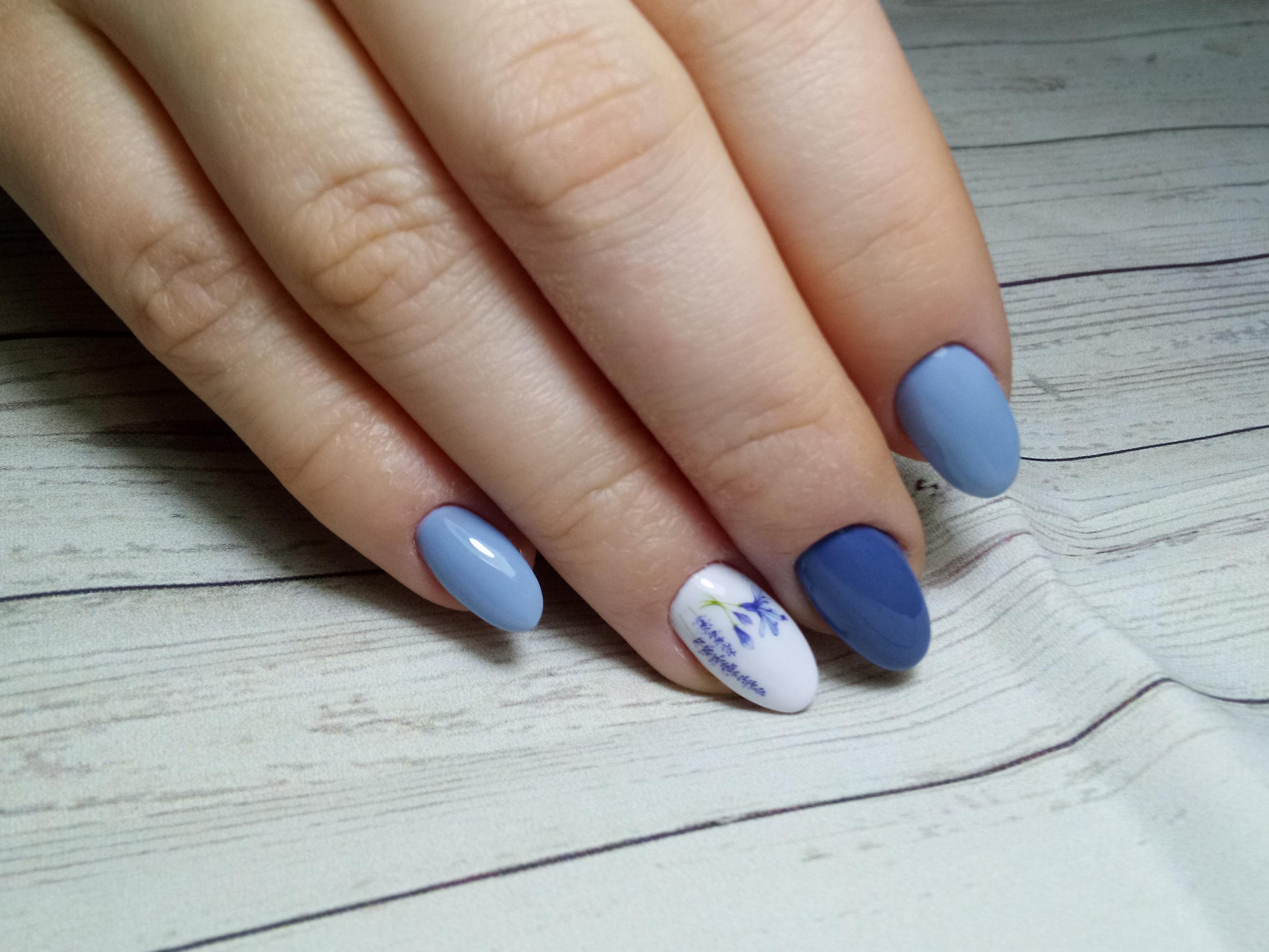 Маникюр в голубом цвете с контрастным дизайном и цветочным рисунком.