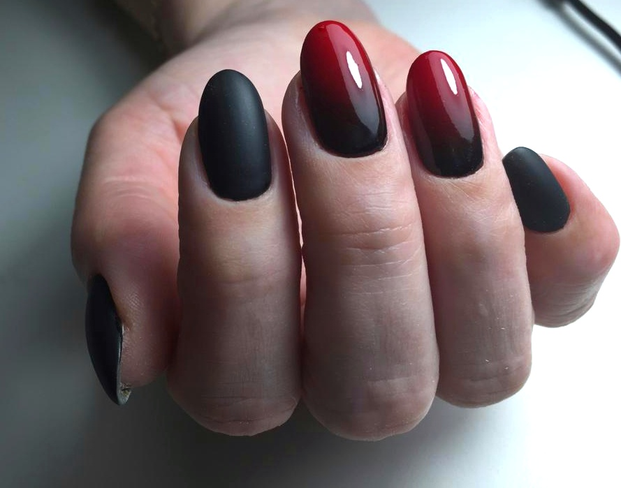 Матовый маникюр в чёрном цвете с глянцевым бордовым градиентом.