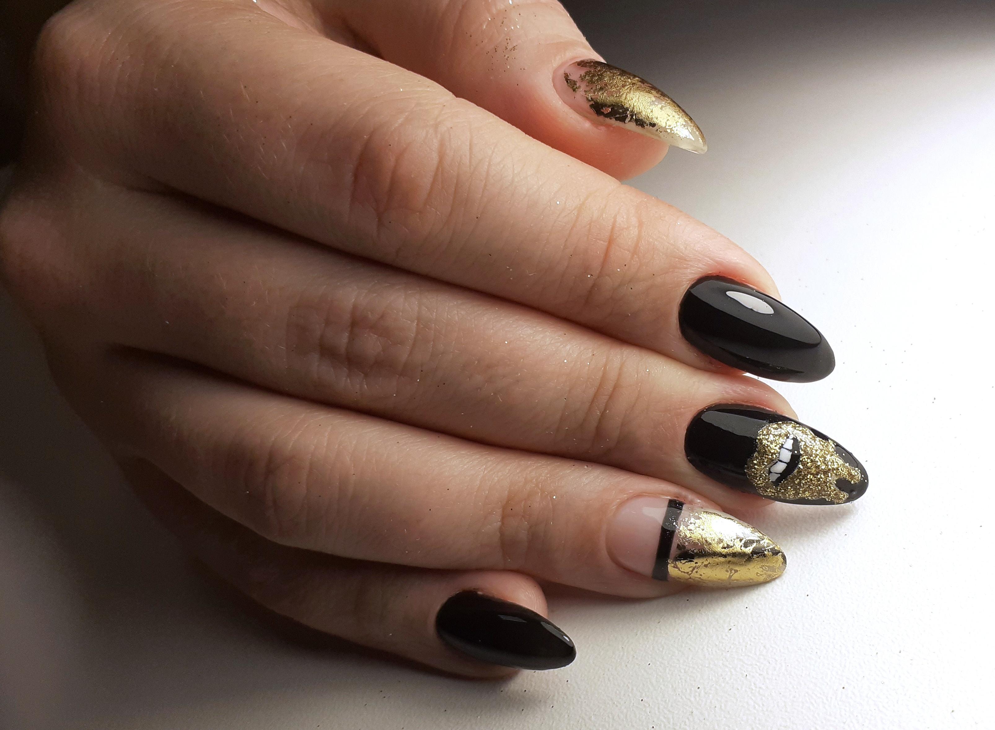 Маникюр с золотыми блестками и полосками в черном цвете.