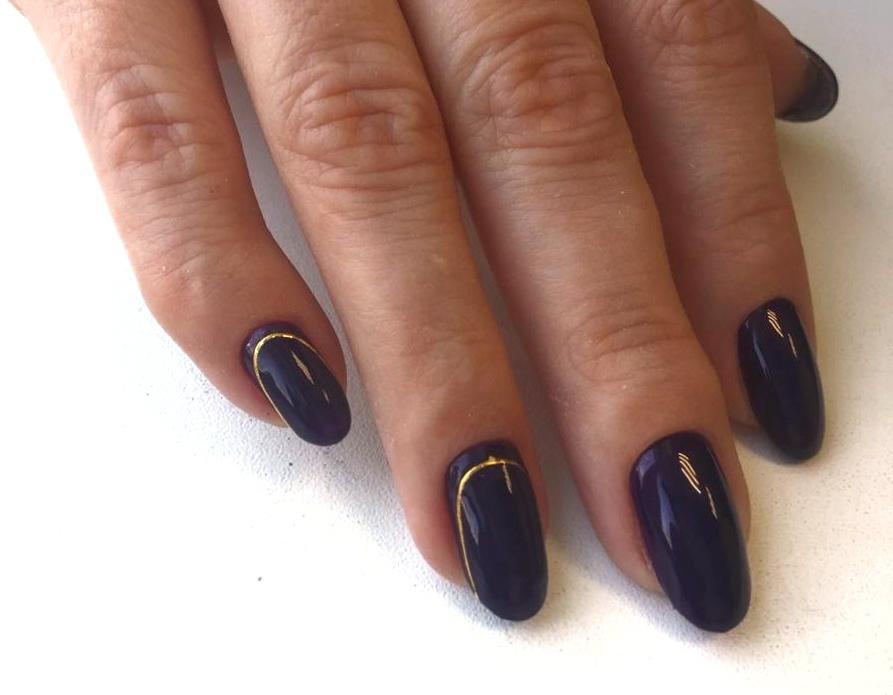 Маникюр с золотыми полосками в темно-синем цвете.