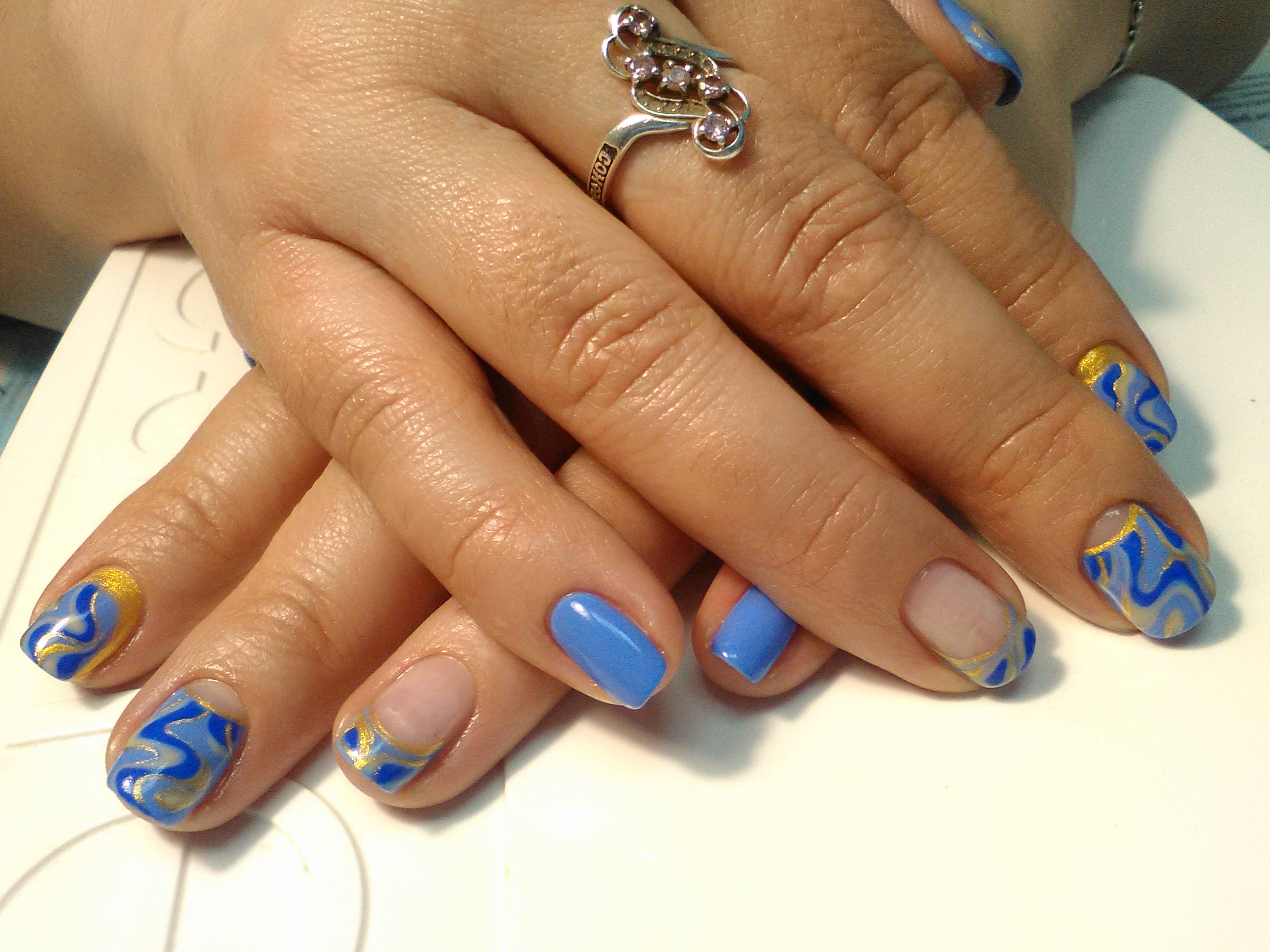 Маникюр в голубом цвете с абстрактным рисунком и золотыми блёстками.