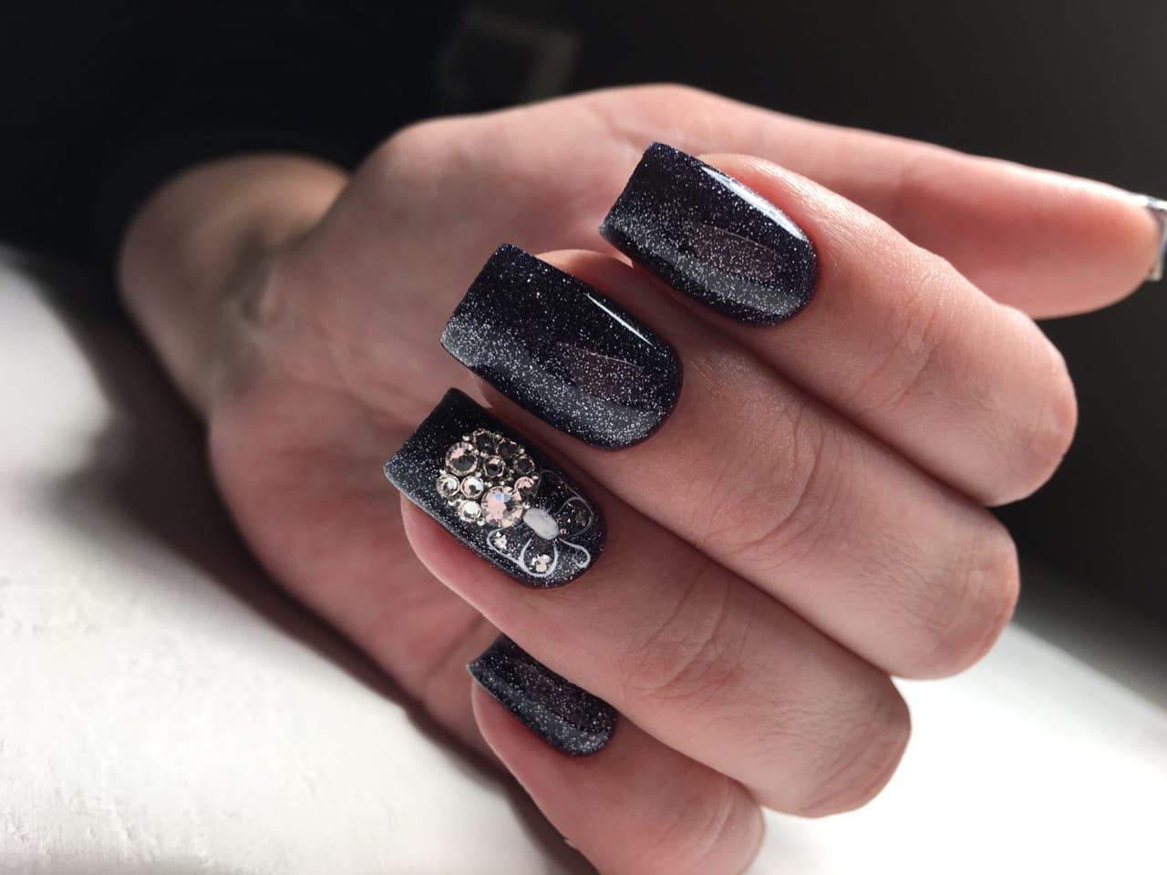 Маникюр в чёрном цвете с серебряными блёстками и новогодним рисунком.