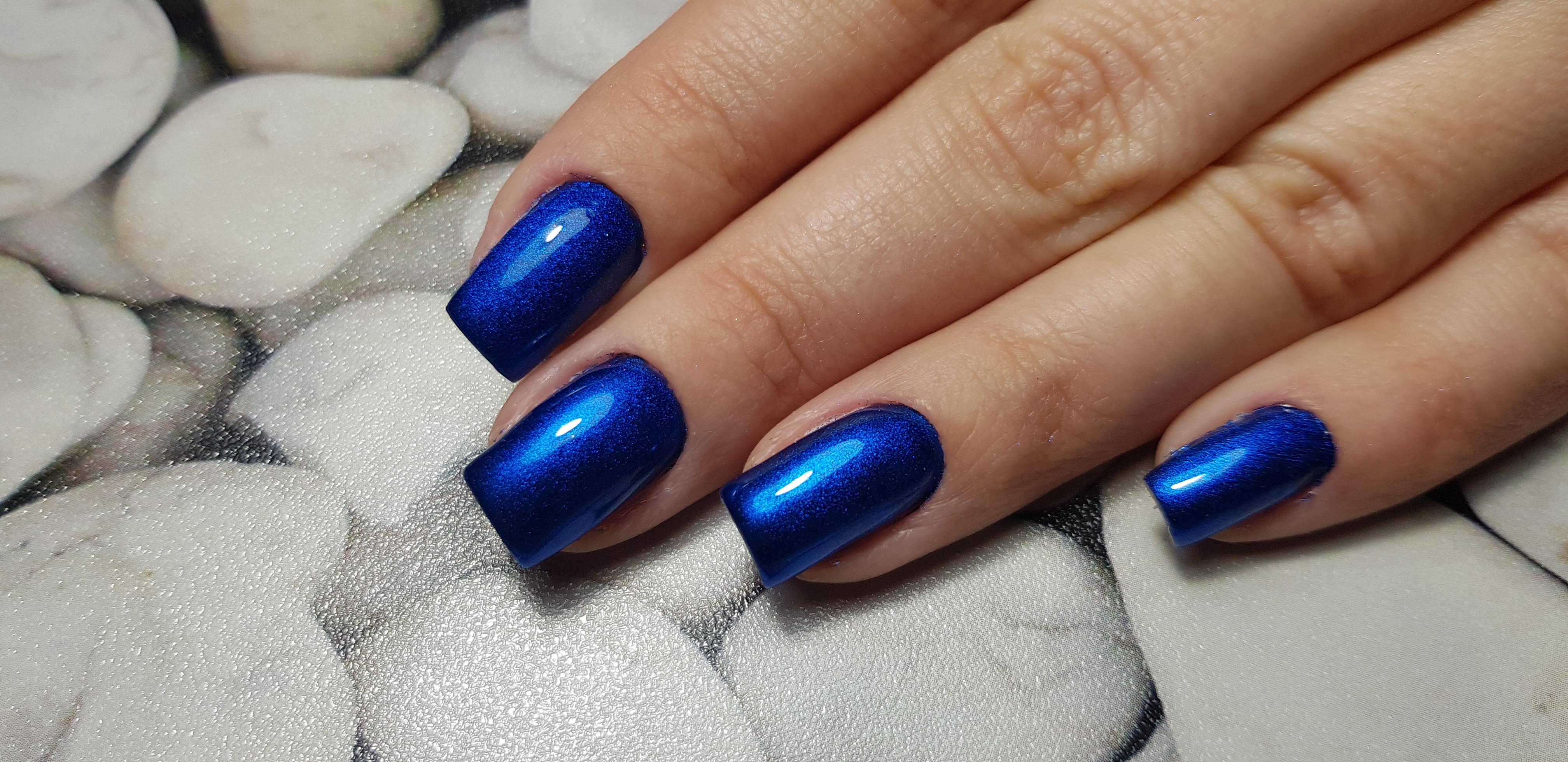 Блестящий однотонный маникюр в синем цвете.